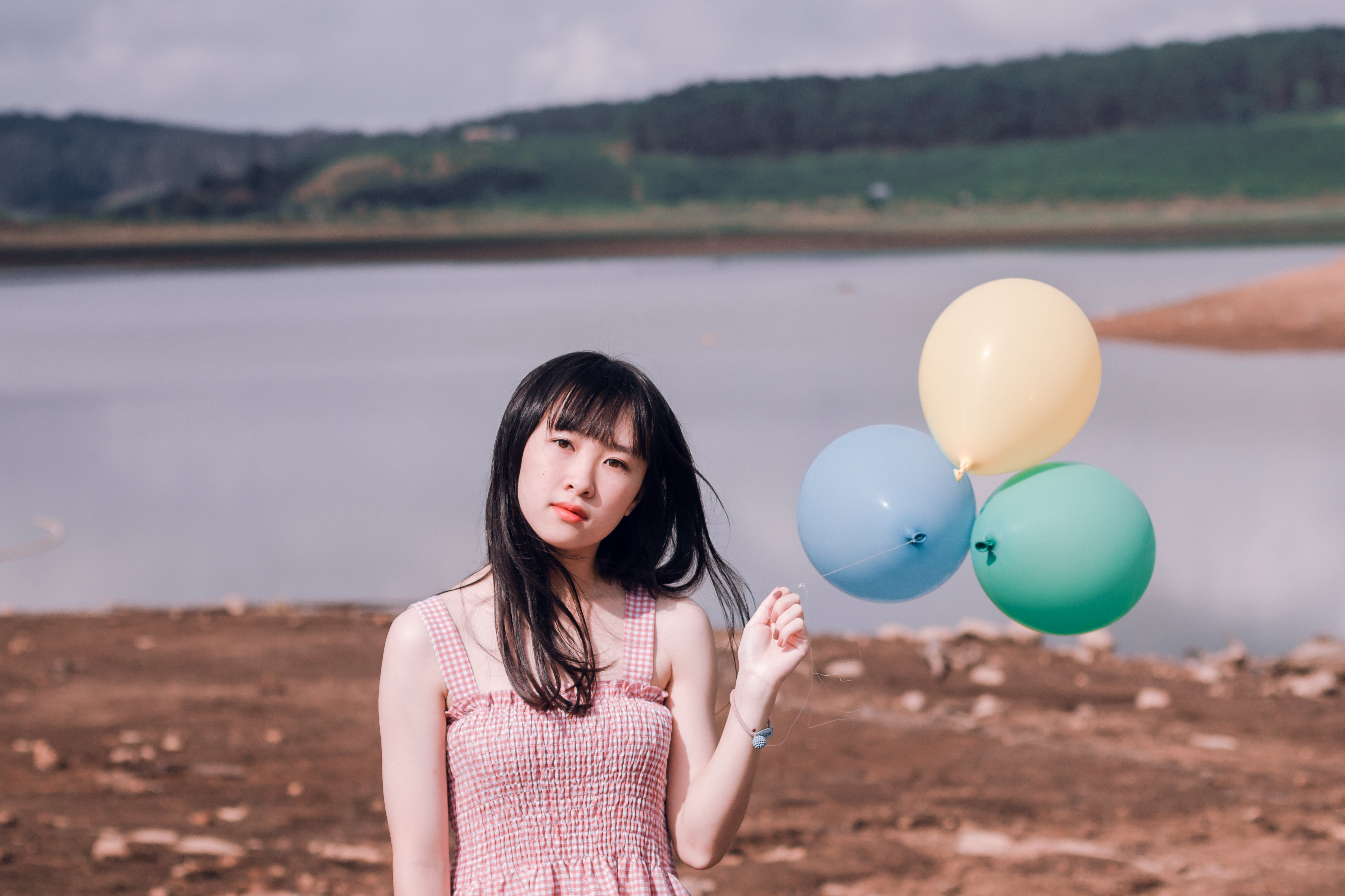 Girl in Pink Sleeveless Top Holds Three Party Balloons