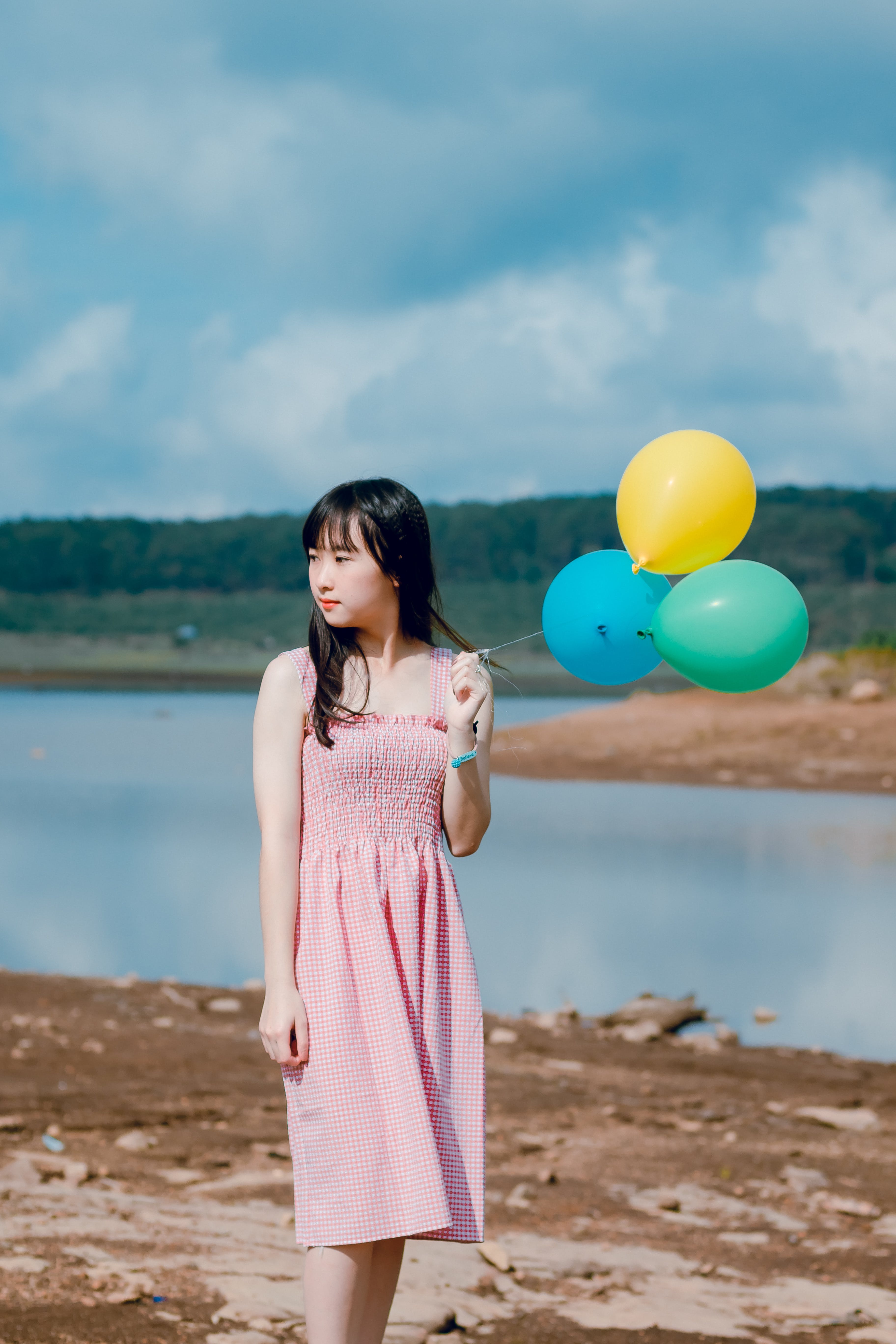 Woman Wearing Pink Dress Holding Three Balloons Near Body of Water