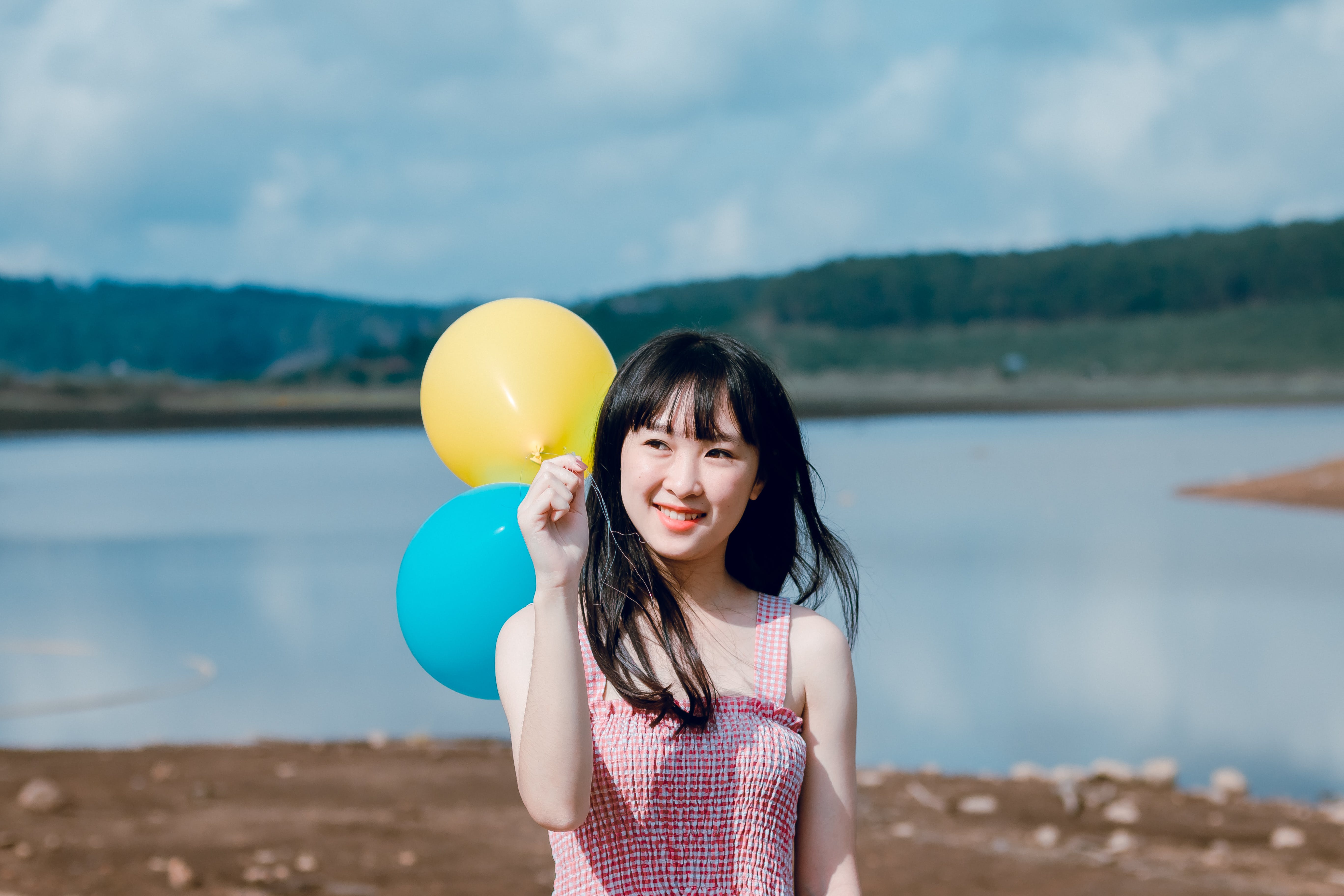Woman in Pink Thick Strap Top Holding a Yellow and Blue Balloons