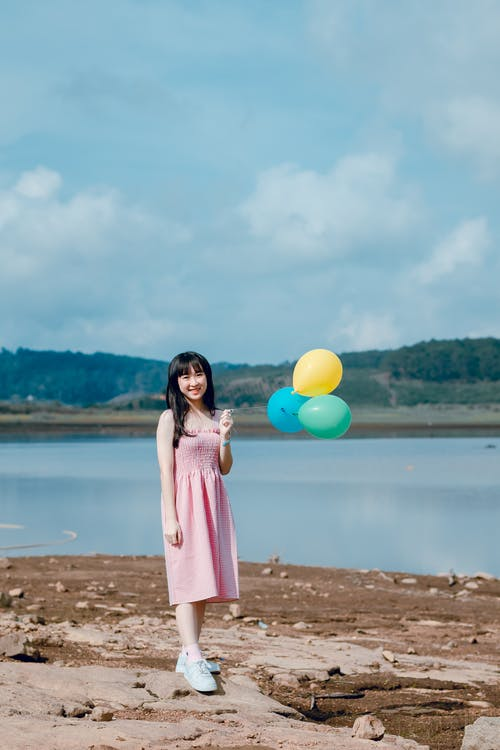 Woman in Pink Dress Holding Balloons