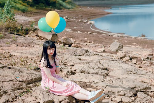 Woman in Pink Thick Strap Dress Holding a Yellow and Blue Balloons While Sitting on Rock Terrain