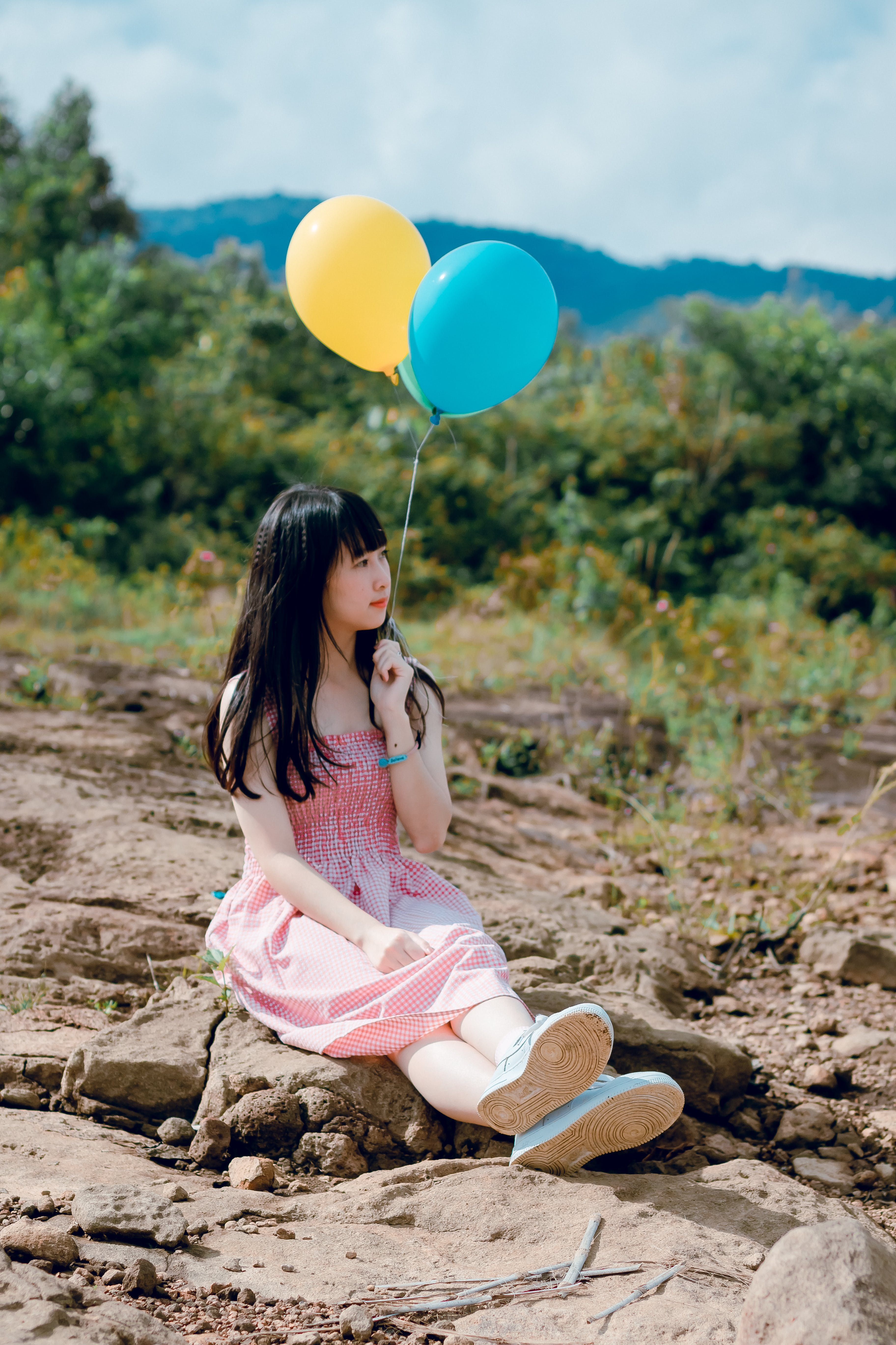 Woman Wearing Pink Dress Sitting on Ground Holding Two Balloons