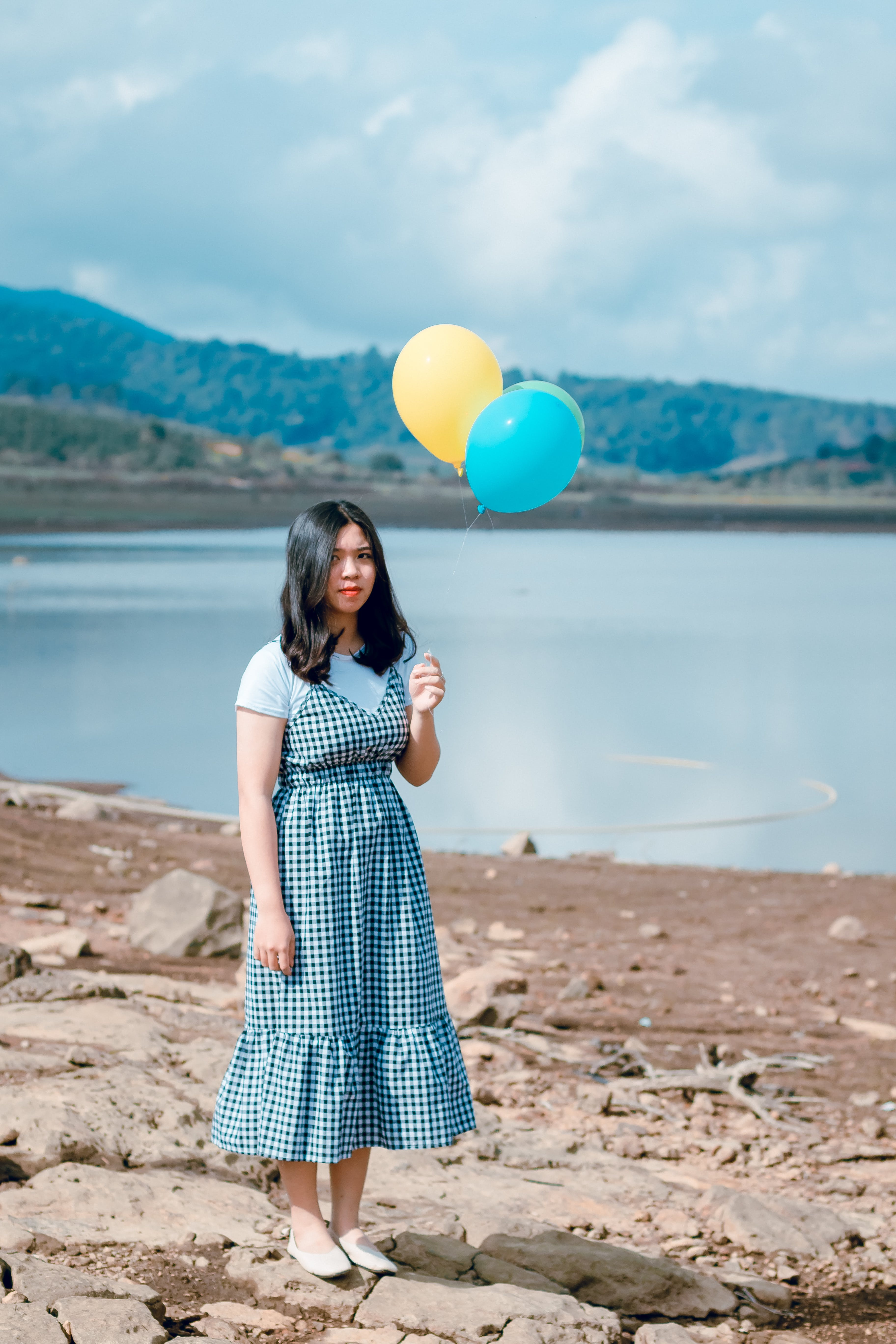 Woman in White and Black Dress Stands While Holding Party Balloons