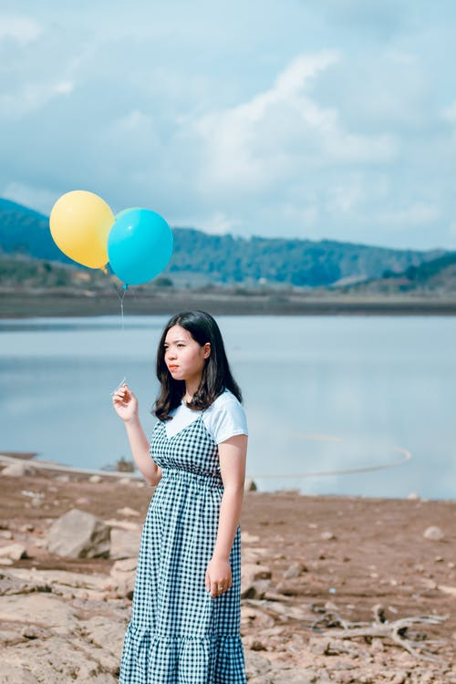 Woman Wearing Blue and White Plaid Dress Holding Blue and Yellow Balloons Near Calm Body of Water at Daytime