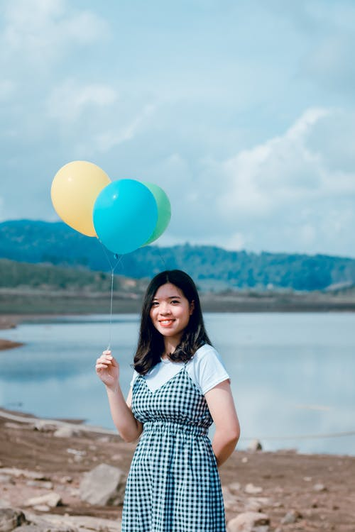 Shallow Focus Photography of Woman in White and Black Short-sleeved Dress Holding Balloons