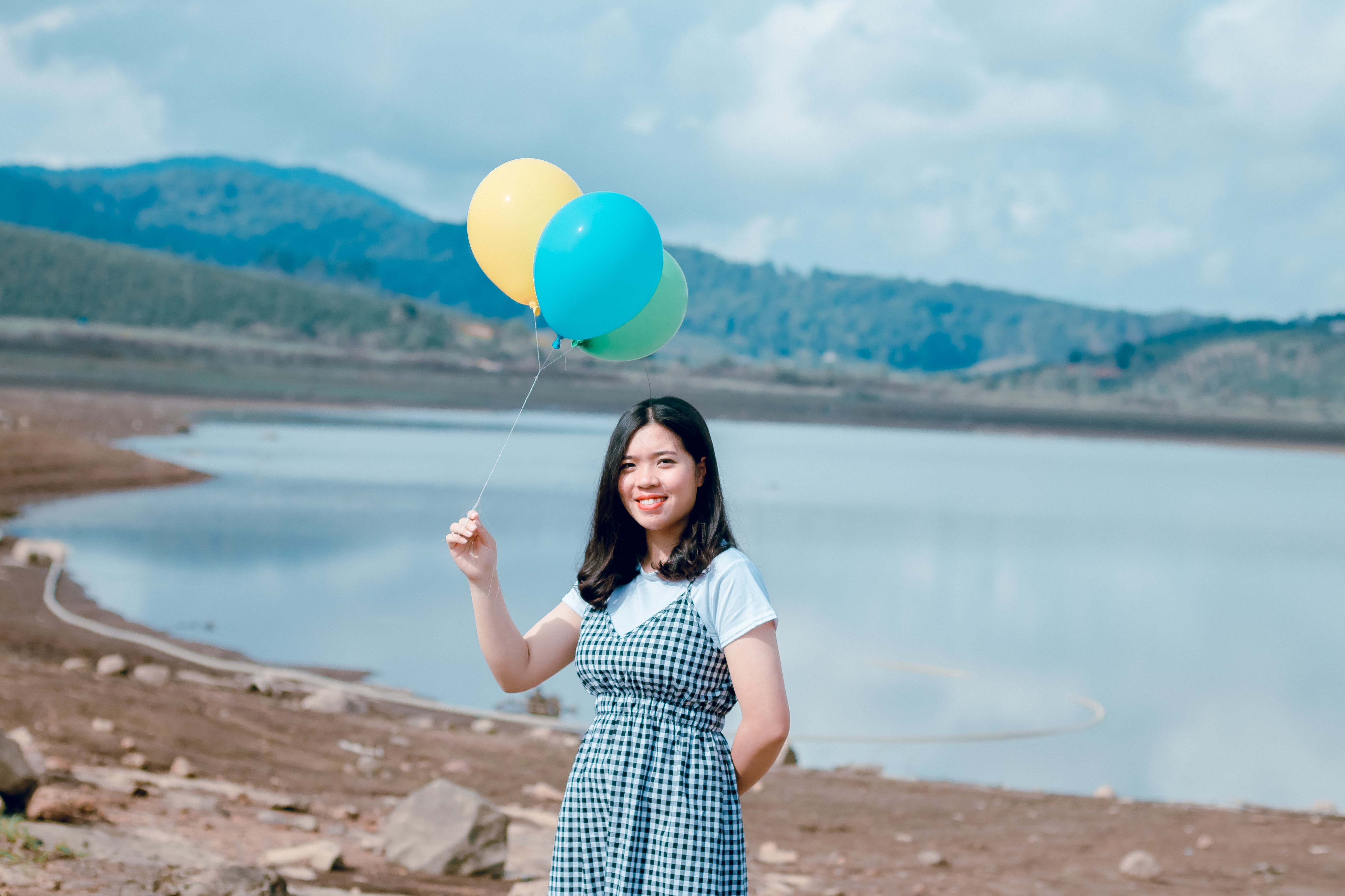 Woman Near Seashore Holding Balloons