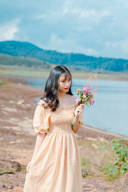 Shallow Focus Photography of Woman in Beige Off-shoulder Dress Holding Bouquet of Flowers