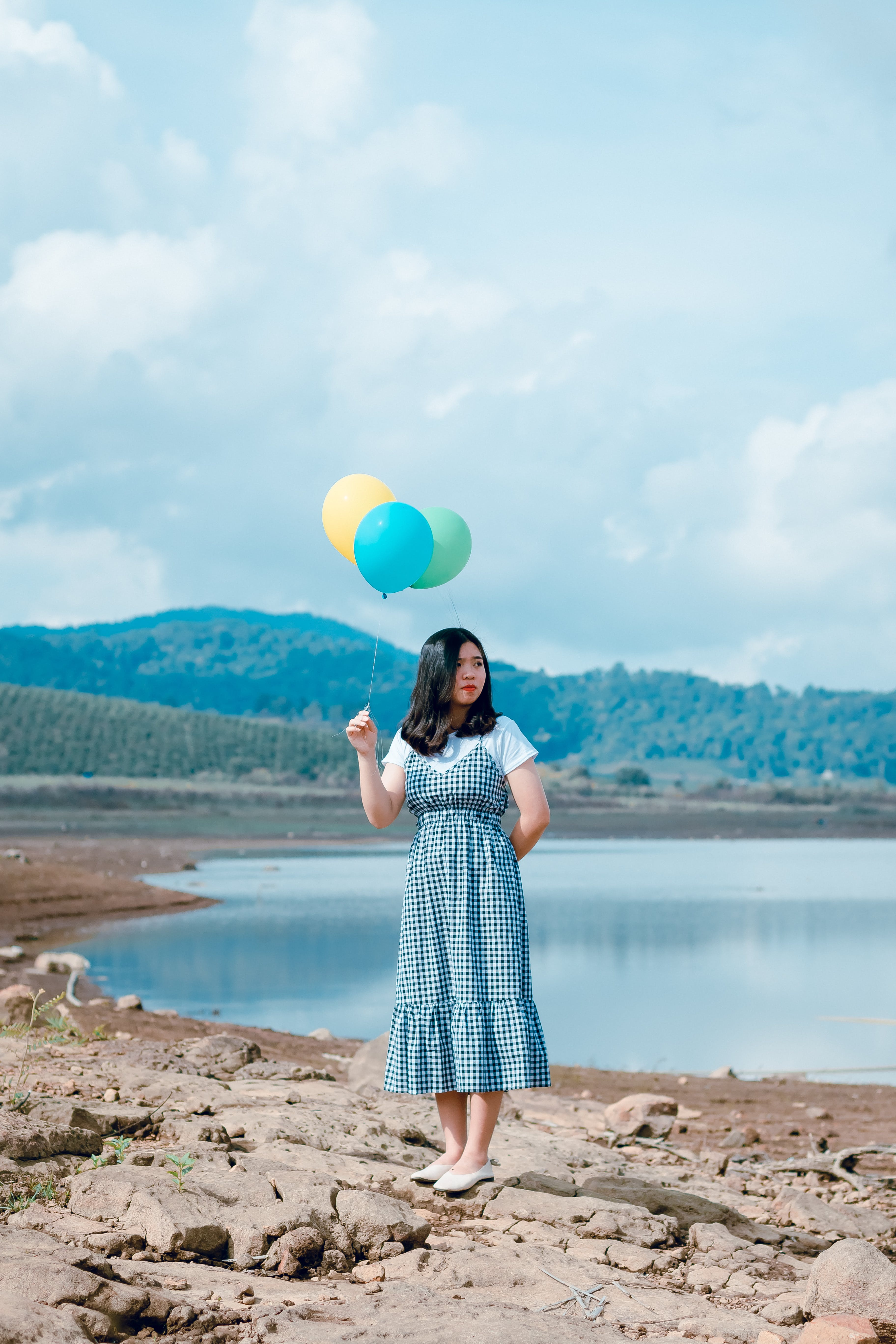 Woman Holding Balloons Near River