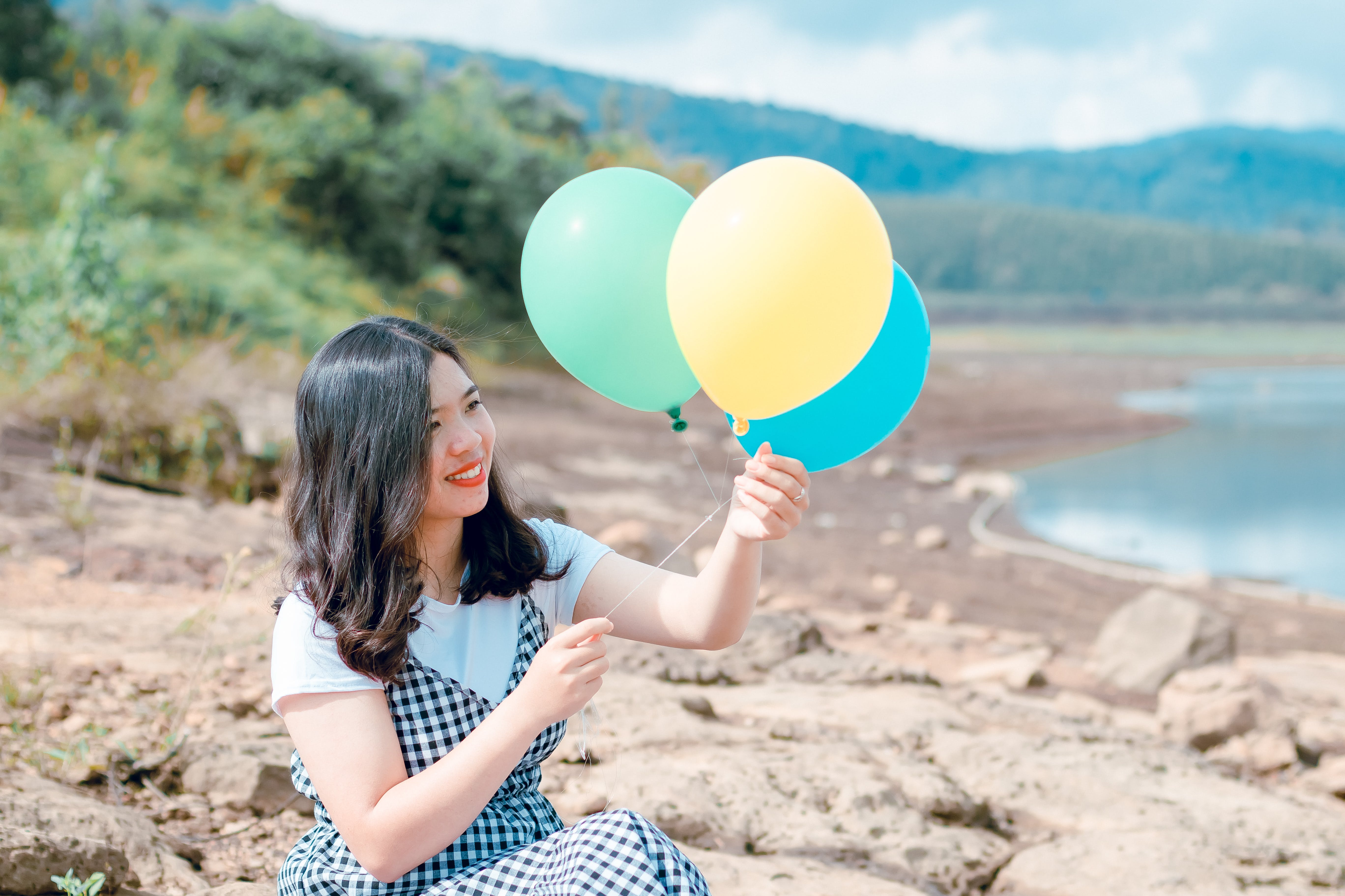 Woman in White and Black Dress Holding Three Balloons