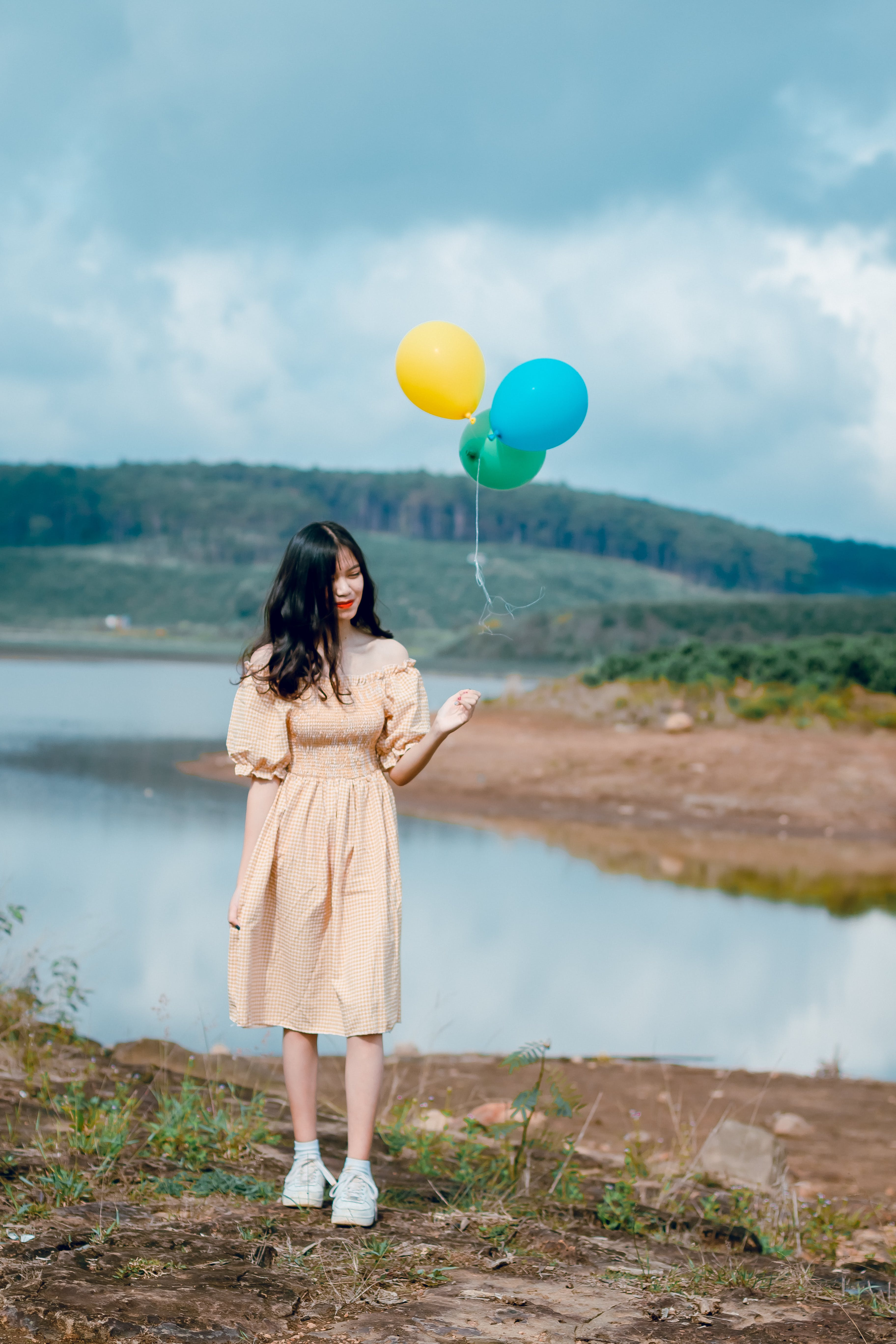 Woman in Beige Off-shoulder Dress Holding Balloons