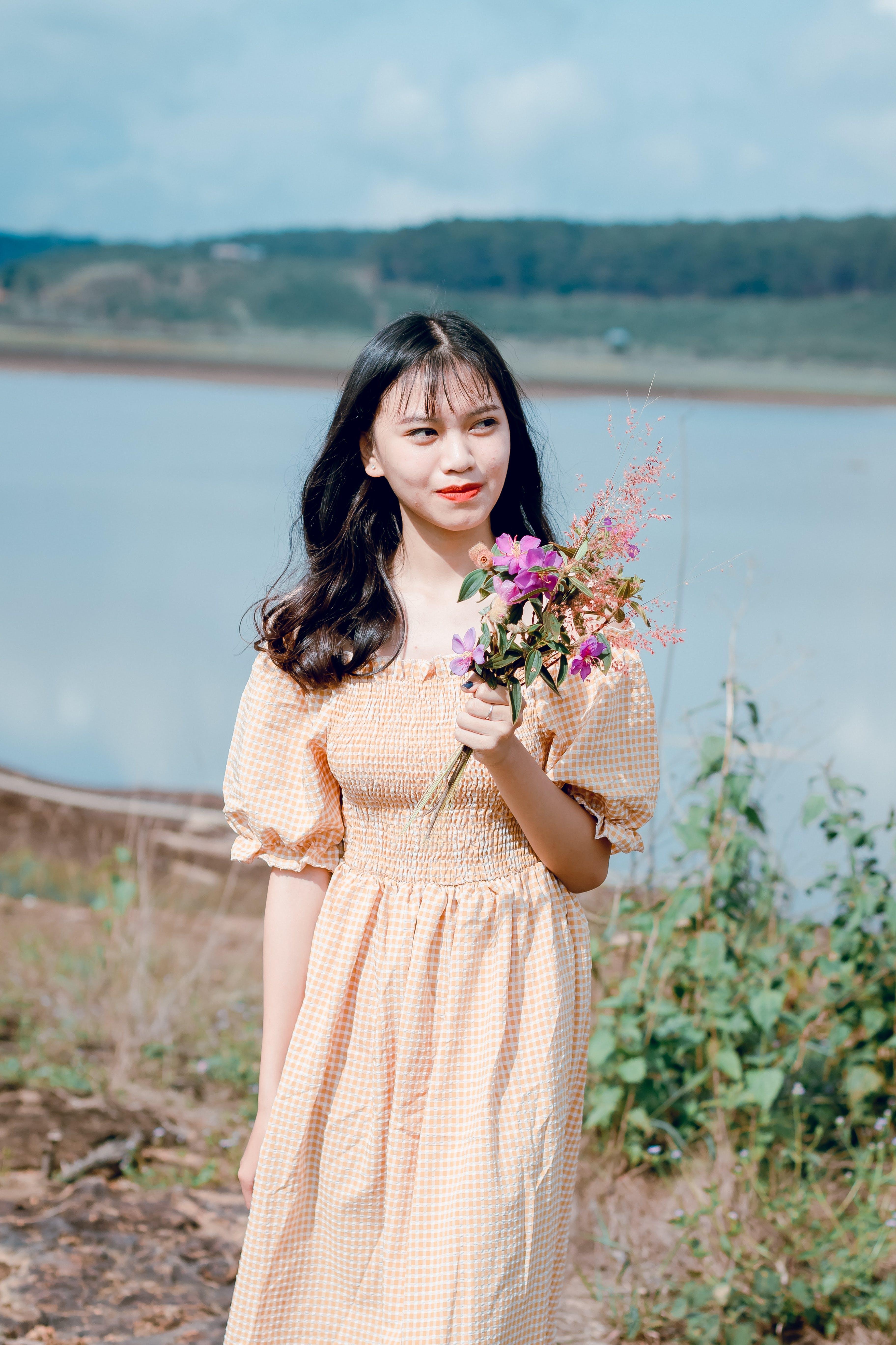 Woman Holding Purple Petaled Flowers