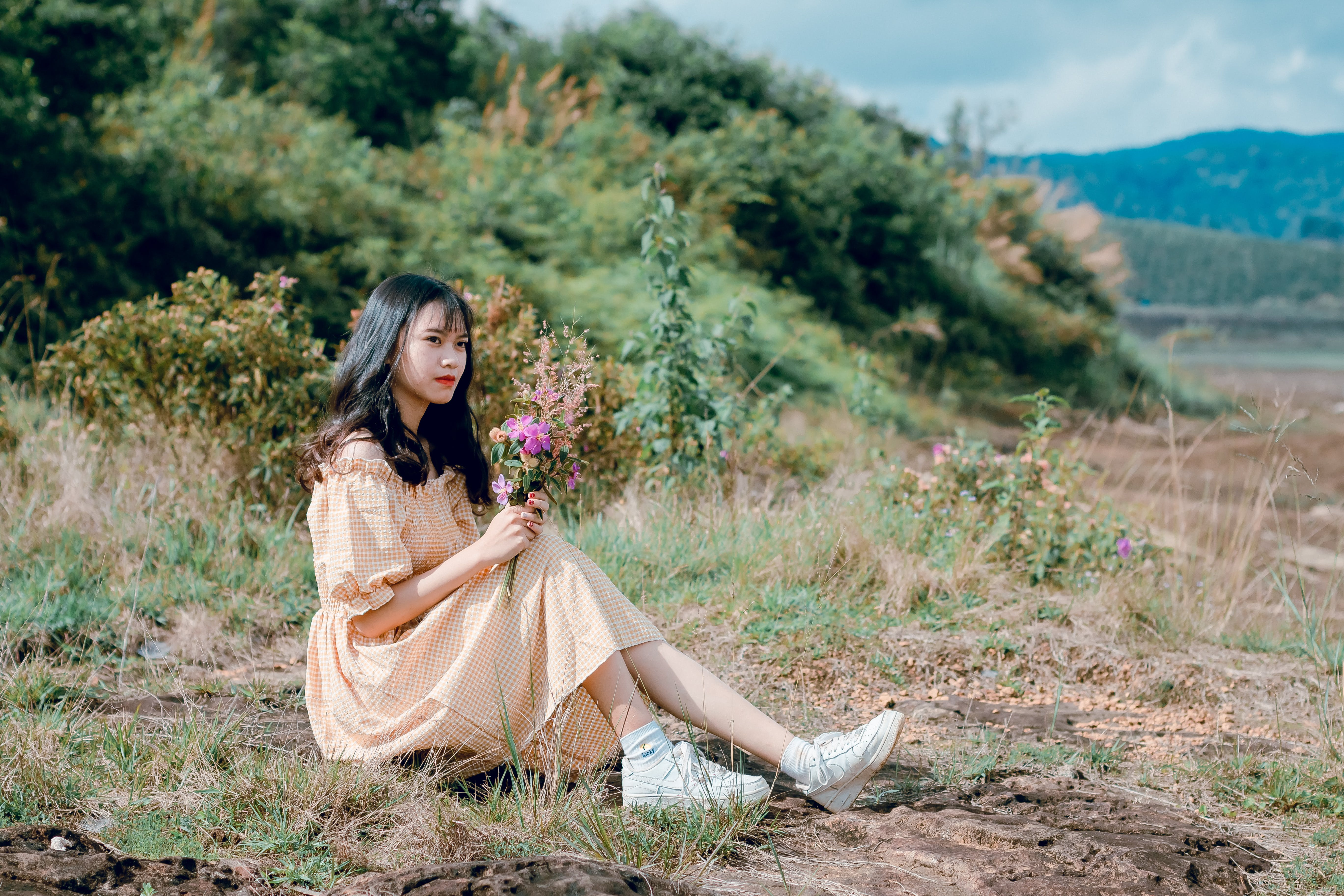 Woman With Beige Dress and White Shoes Sitting on Green Grass
