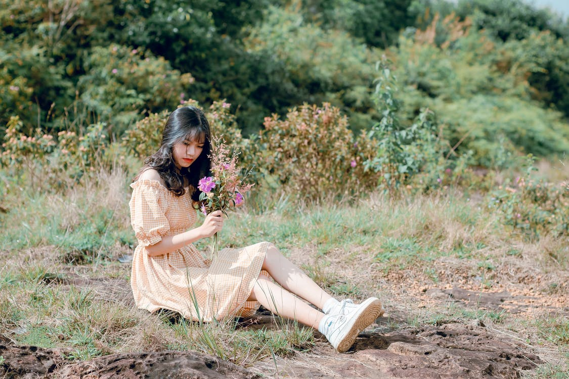 Woman Sitting on Ground and Holding Flower