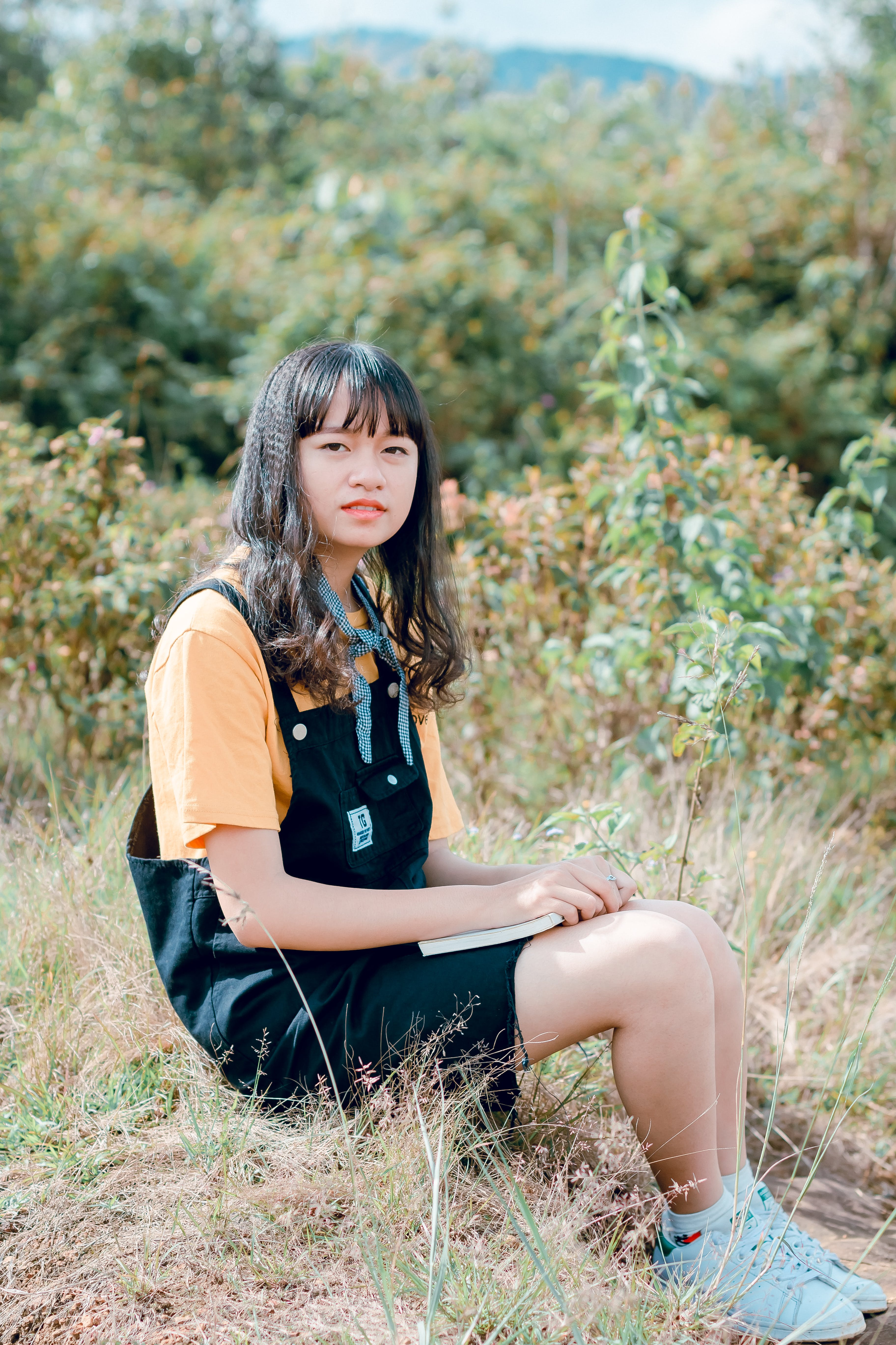 Girl in Black Dungaree and Orange Shirt Sitting of Grass Field