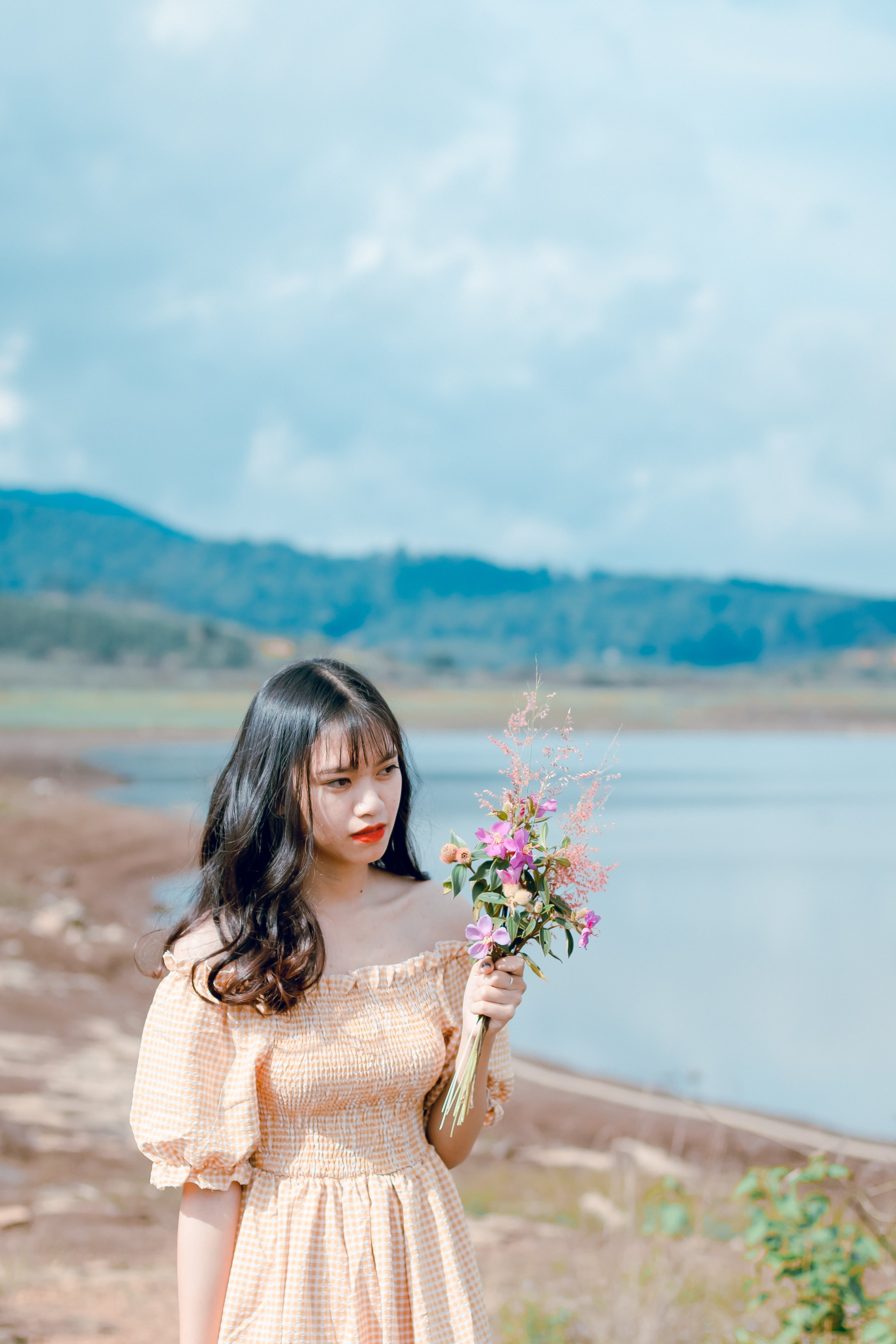 Photography of a Woman Holding Flowers
