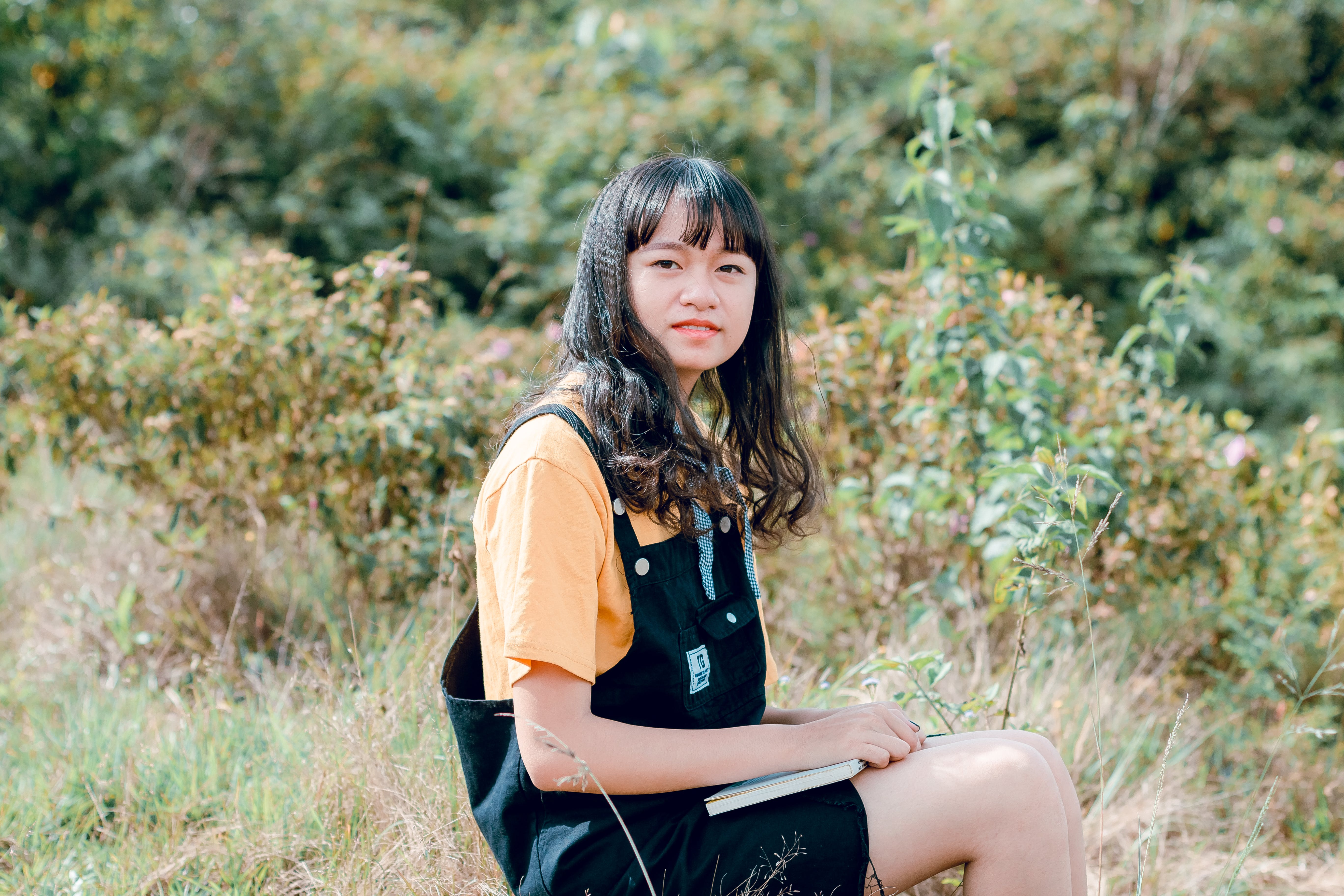 Shallow Focus Photography of Woman in Yellow Shirt and Black Dungaree