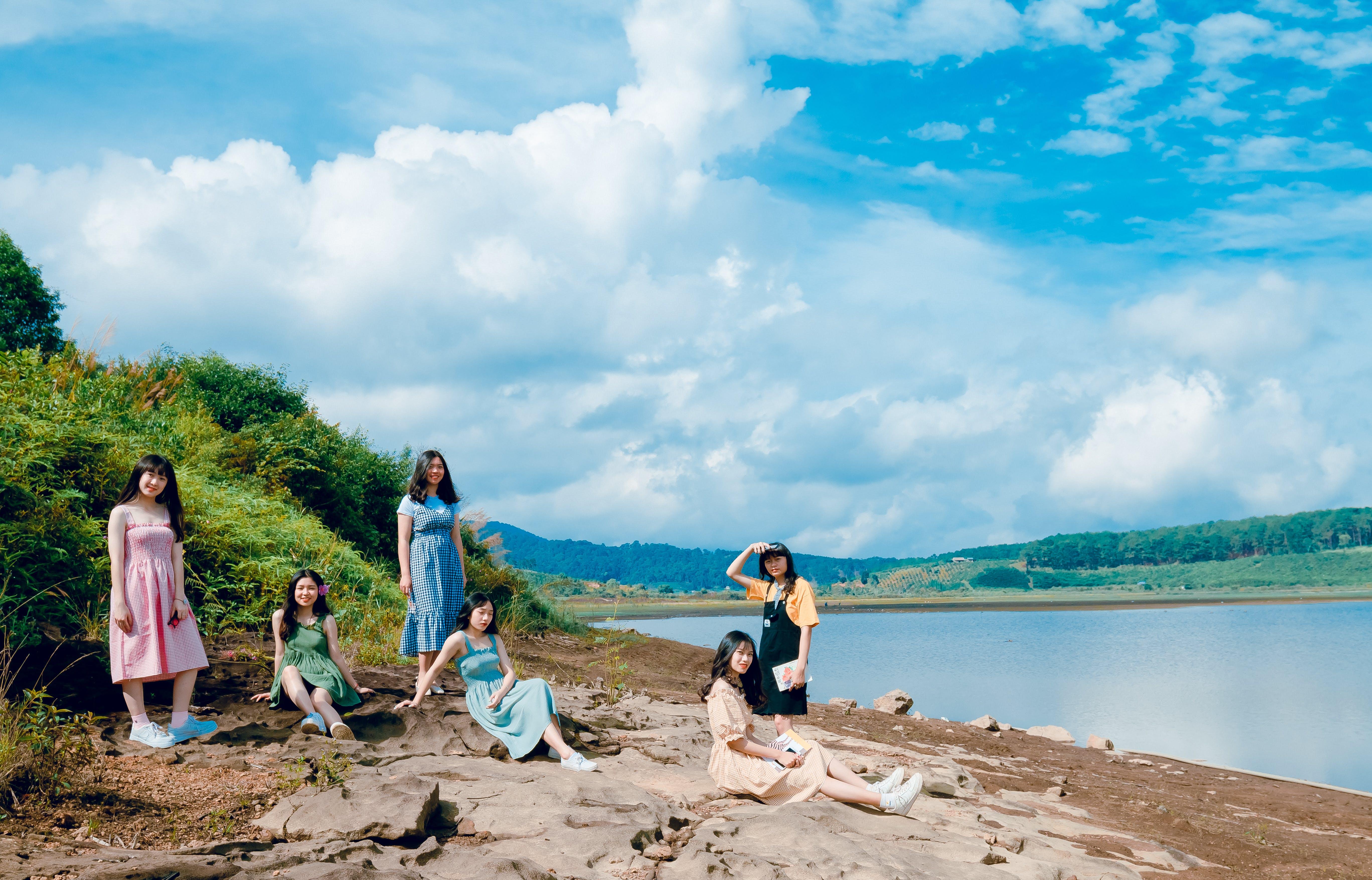 Women Sitting Near Body Of Water