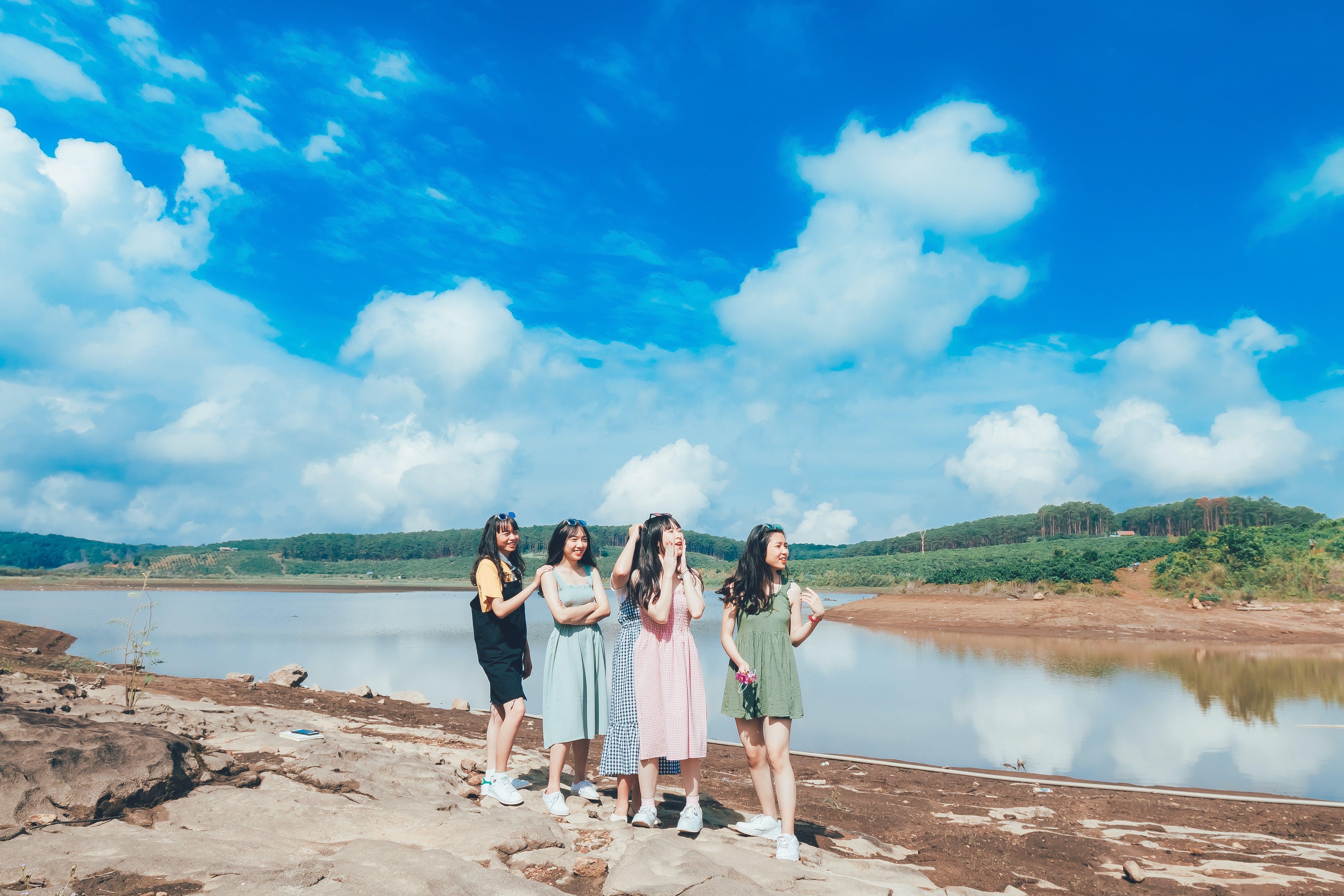 Four Women Standing Near Lake