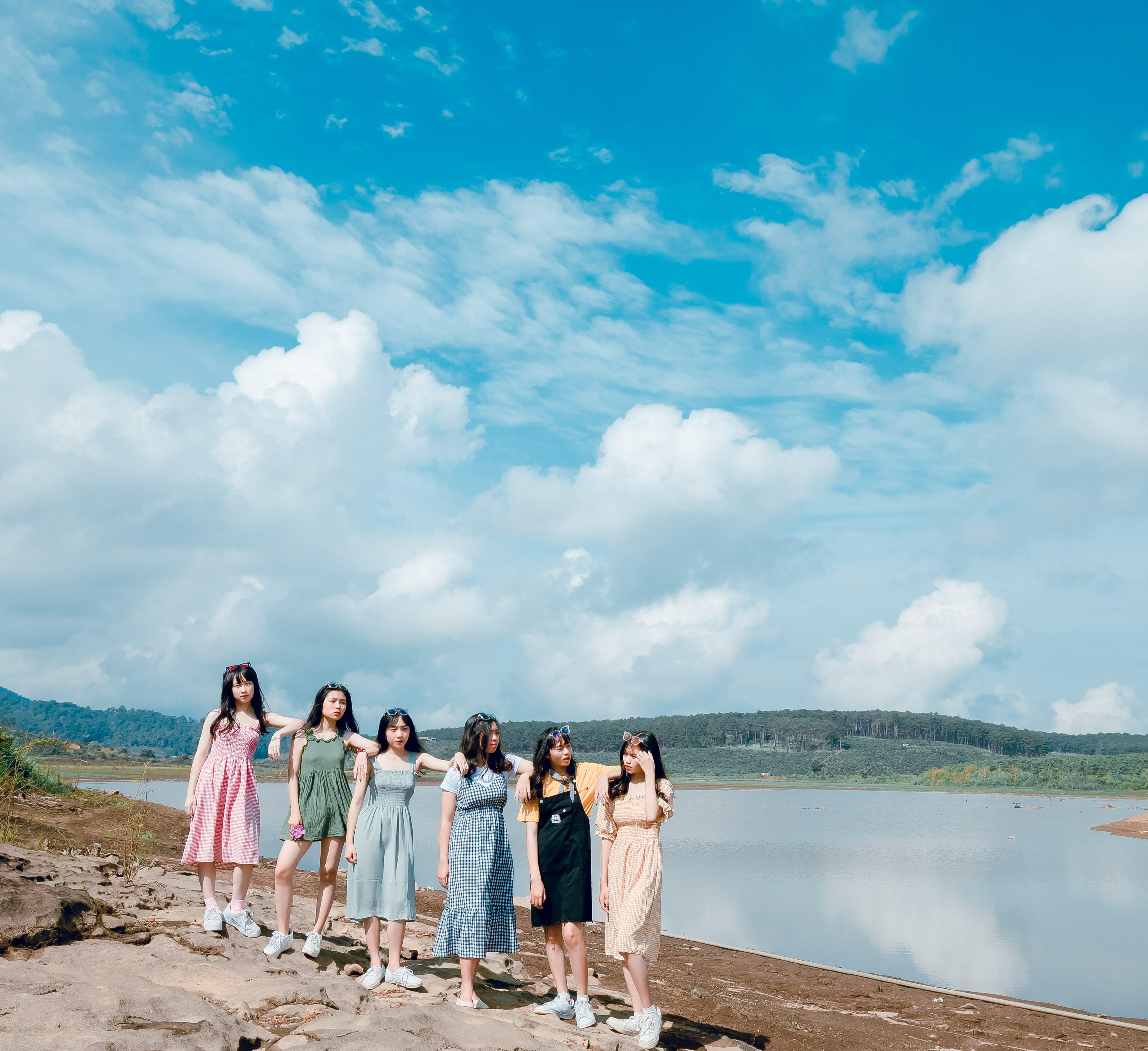 Group of Women Wearing Dress Standing Near Body Of Water