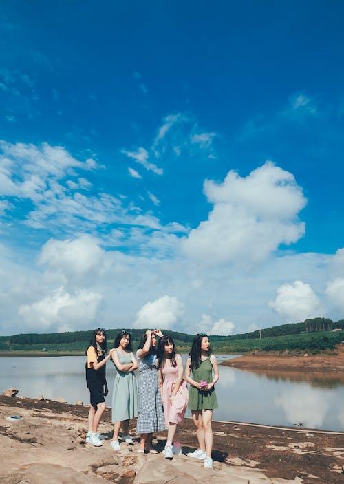 Women Standing Near Body Of Water