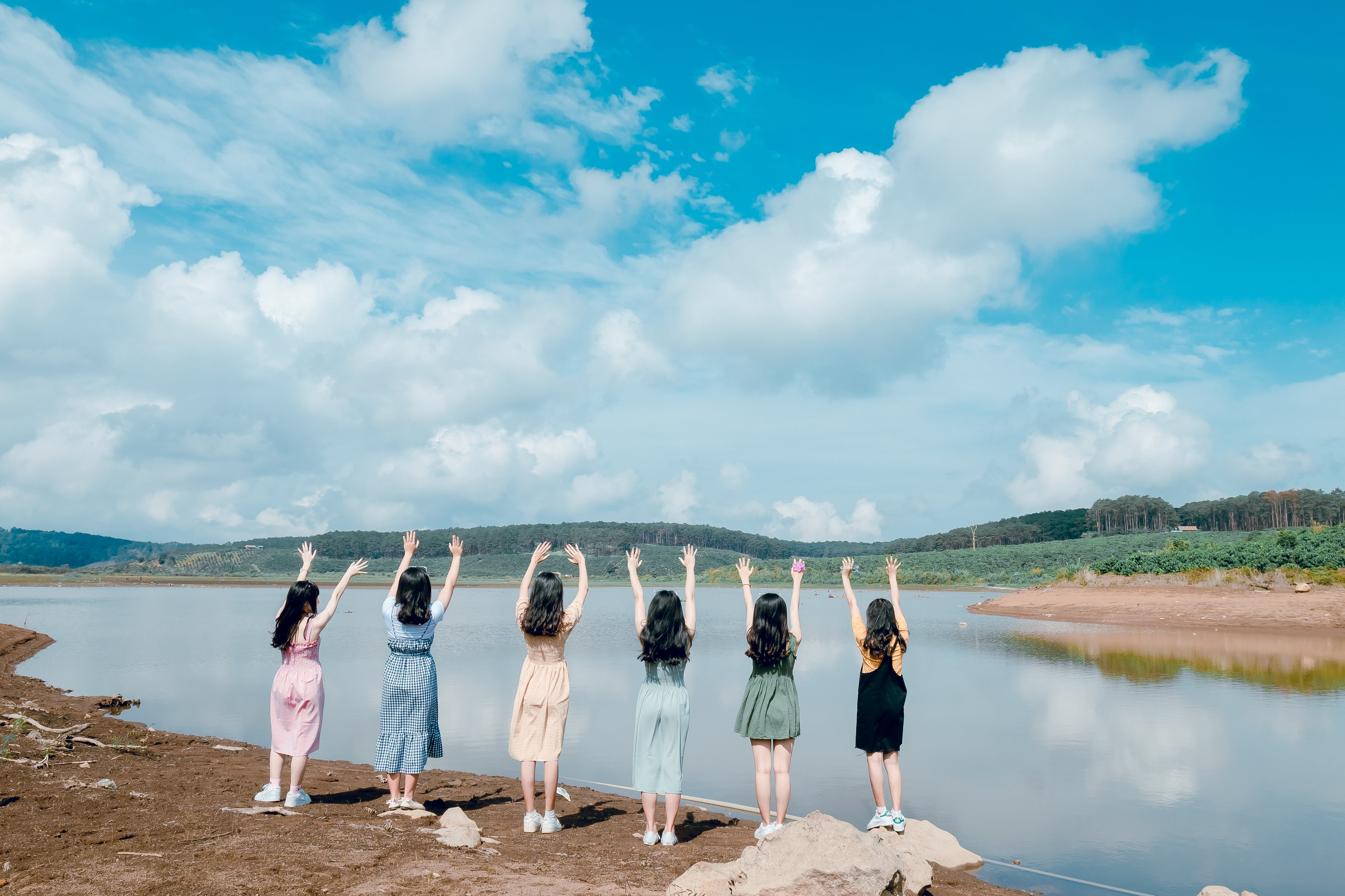 Six Girls Raise Their Hands in Front of Body of Water