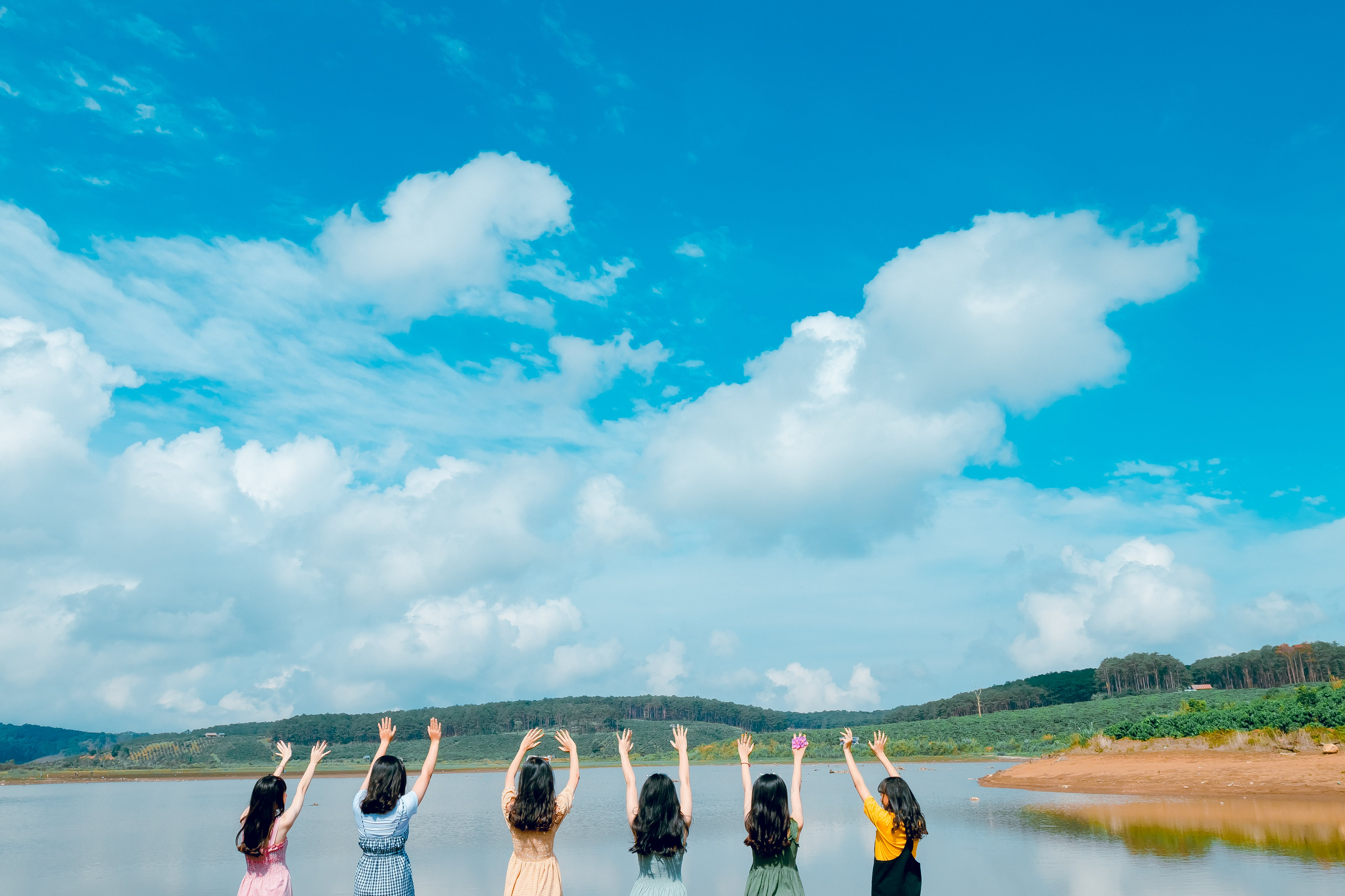 Group of Women Wearing Dress Raising Up Their Hands on Air Under Cloudy Sky