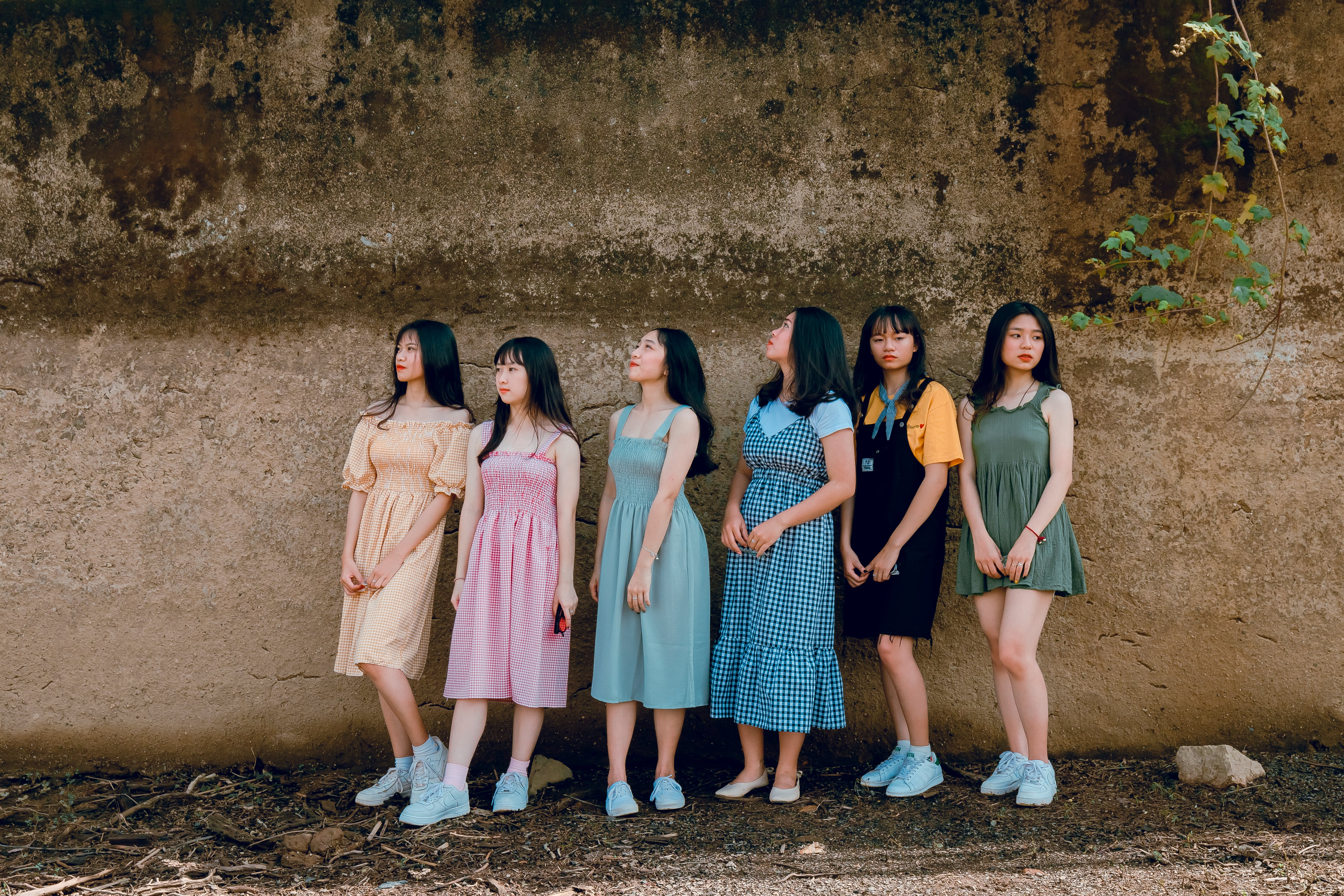 Photography of Six Girl Standing Beside Wall