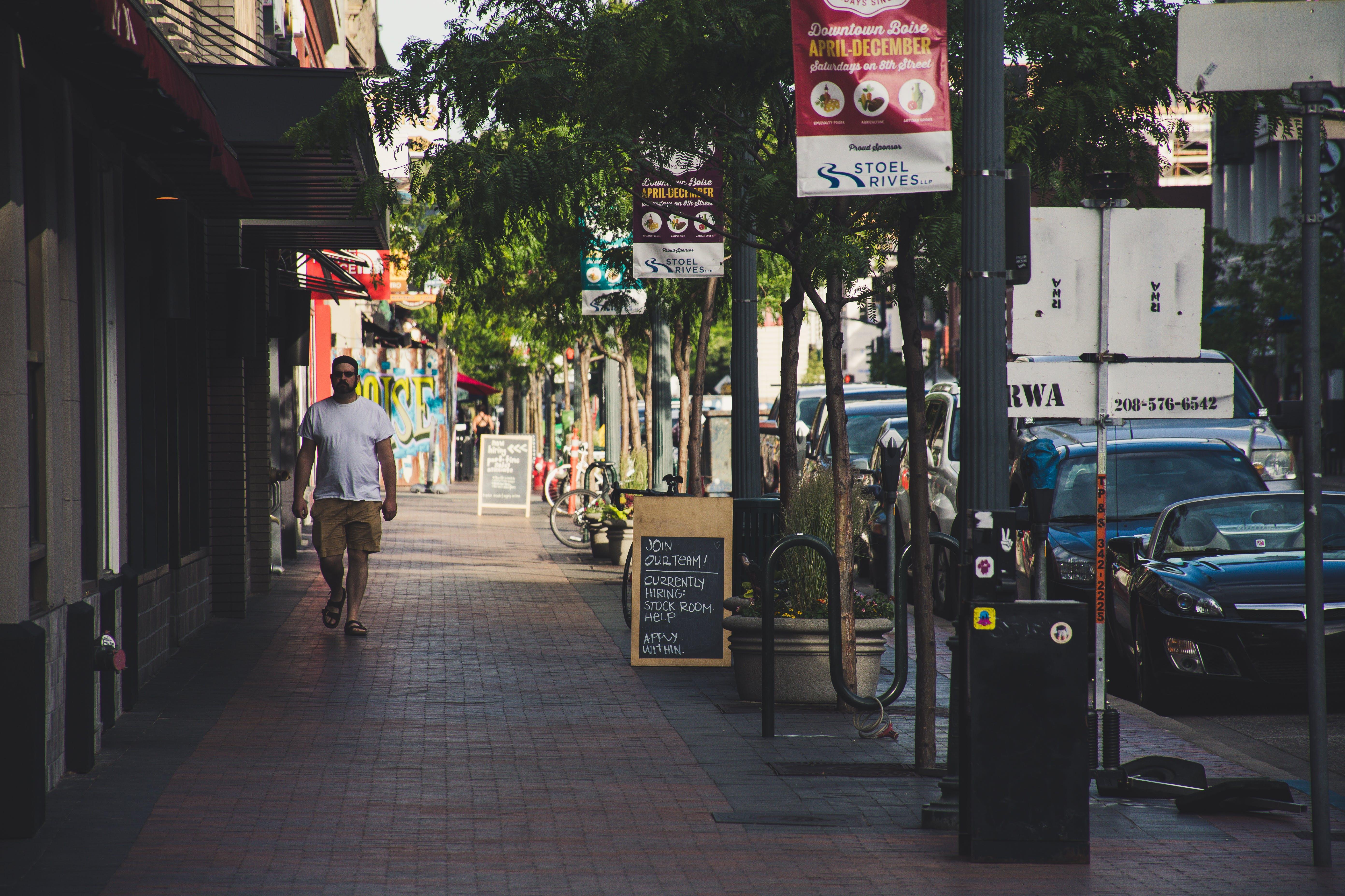 Man Wearing White Crew-neck T-shirt Walking On Sidewalk
