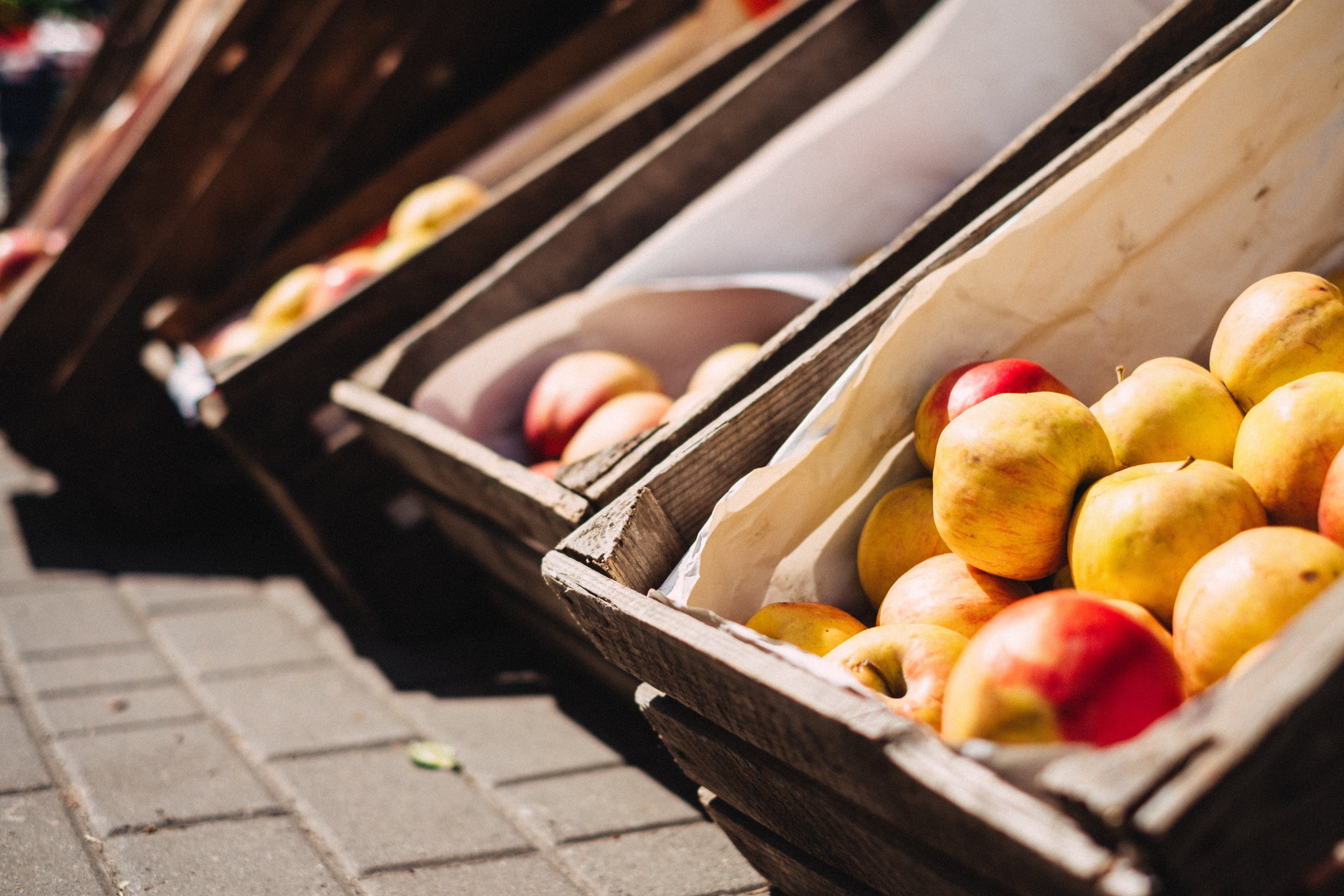 Yellow and Red Apples on Brown Crate