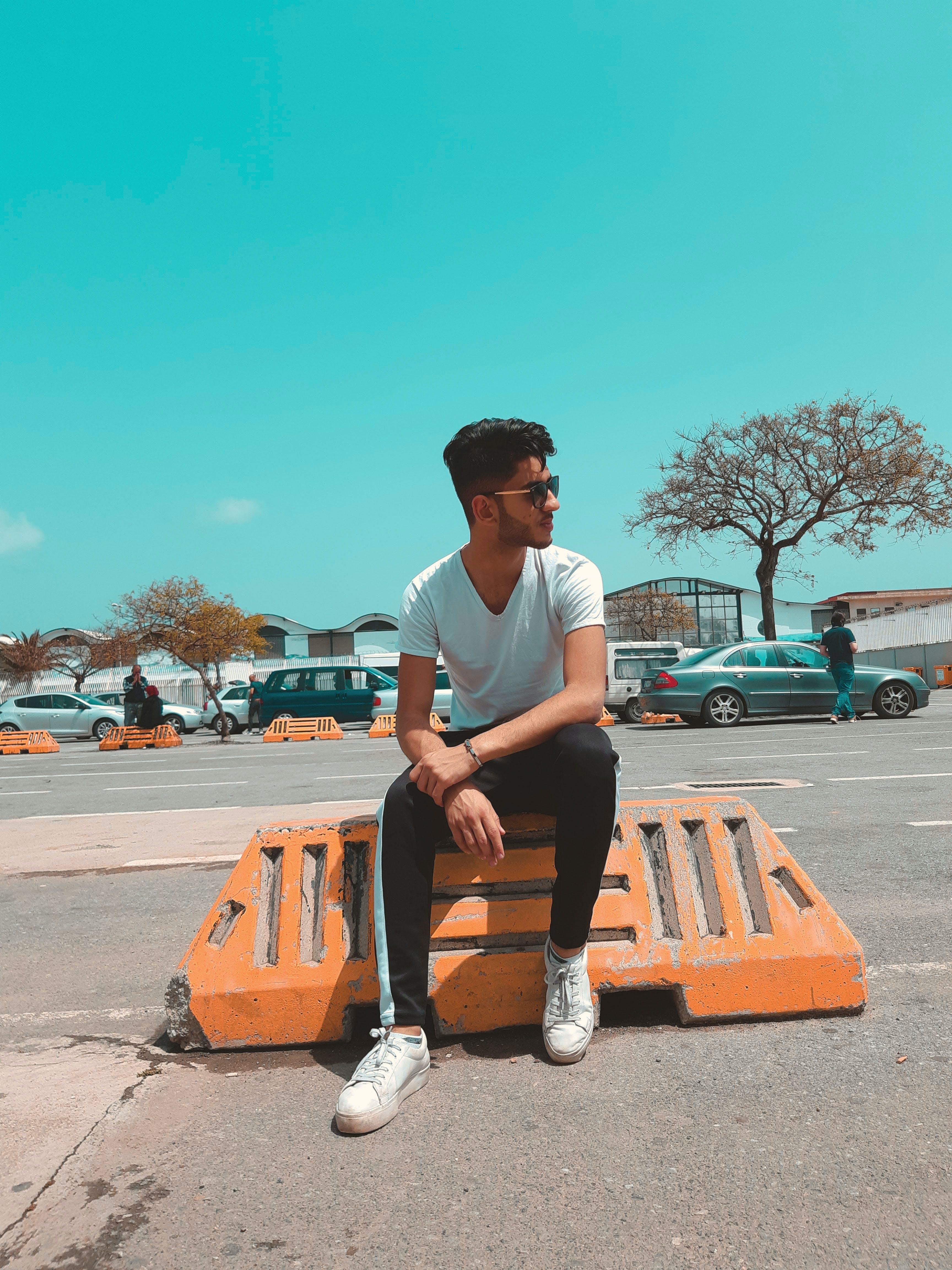 Man In White Shirt Sitting On Orange Concrete