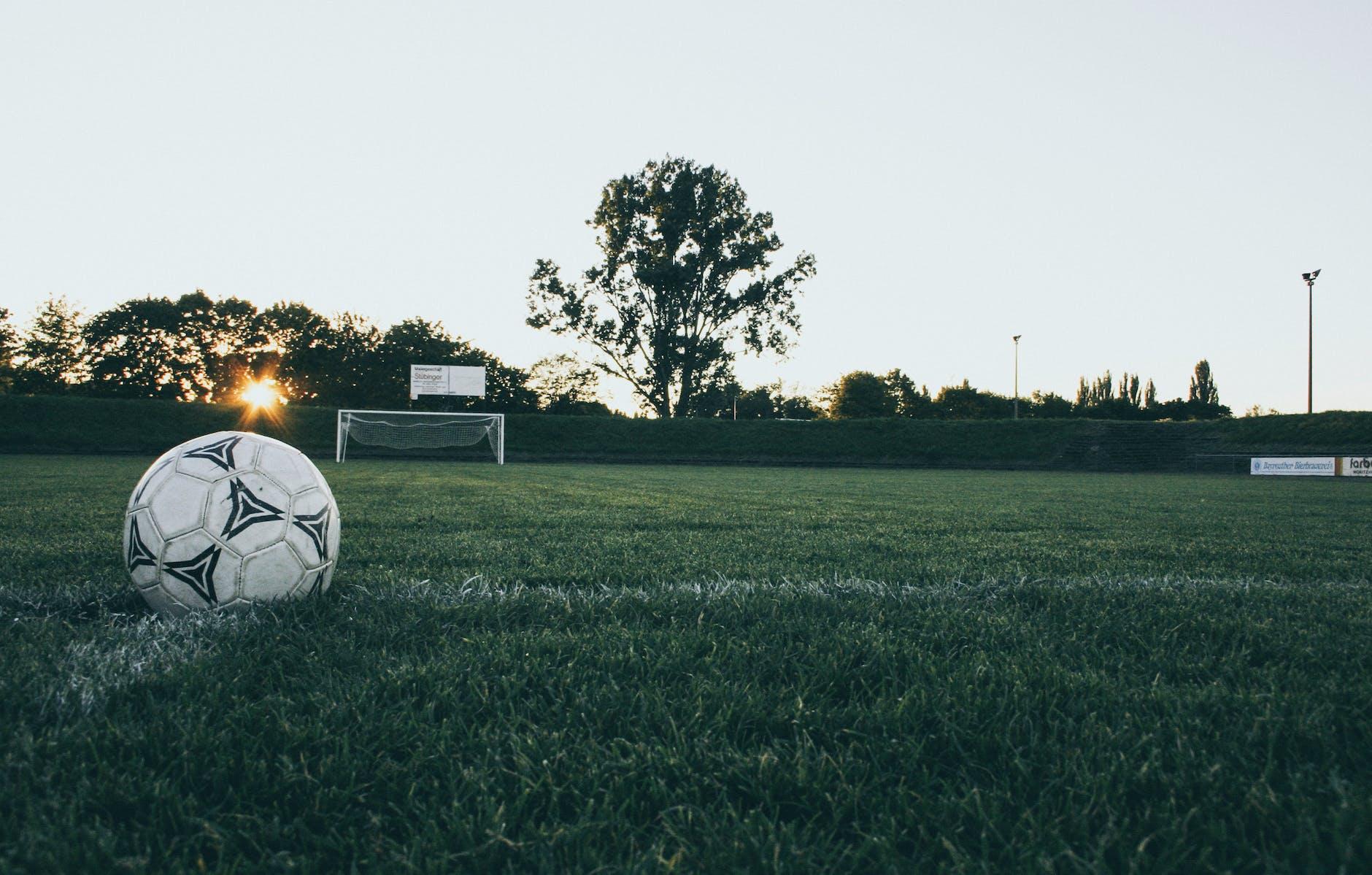 Voetbal op een voetbalveld met ondergaande zon