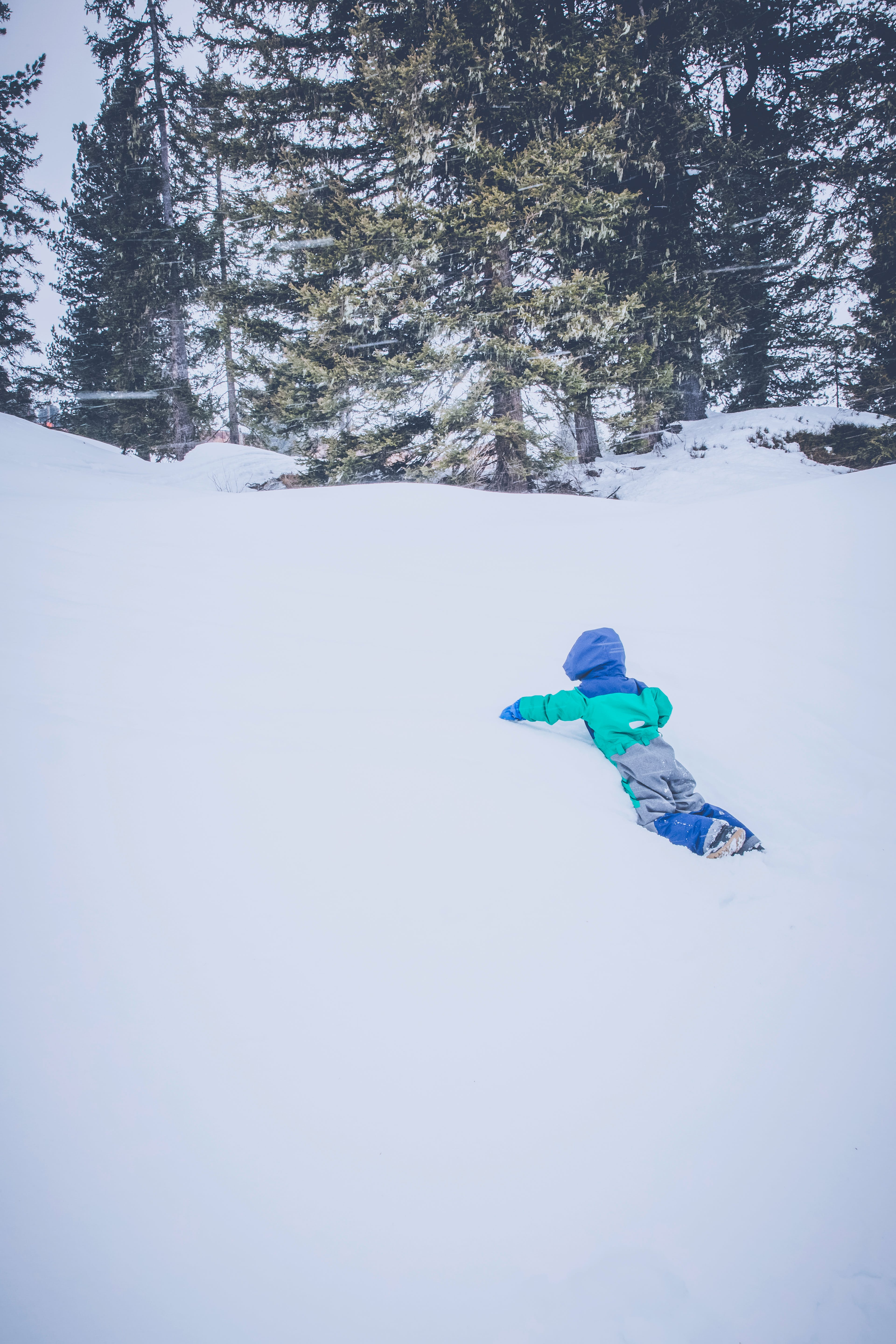 Toddler in Blue and Green Snow Suit on Snow Field during Daytime