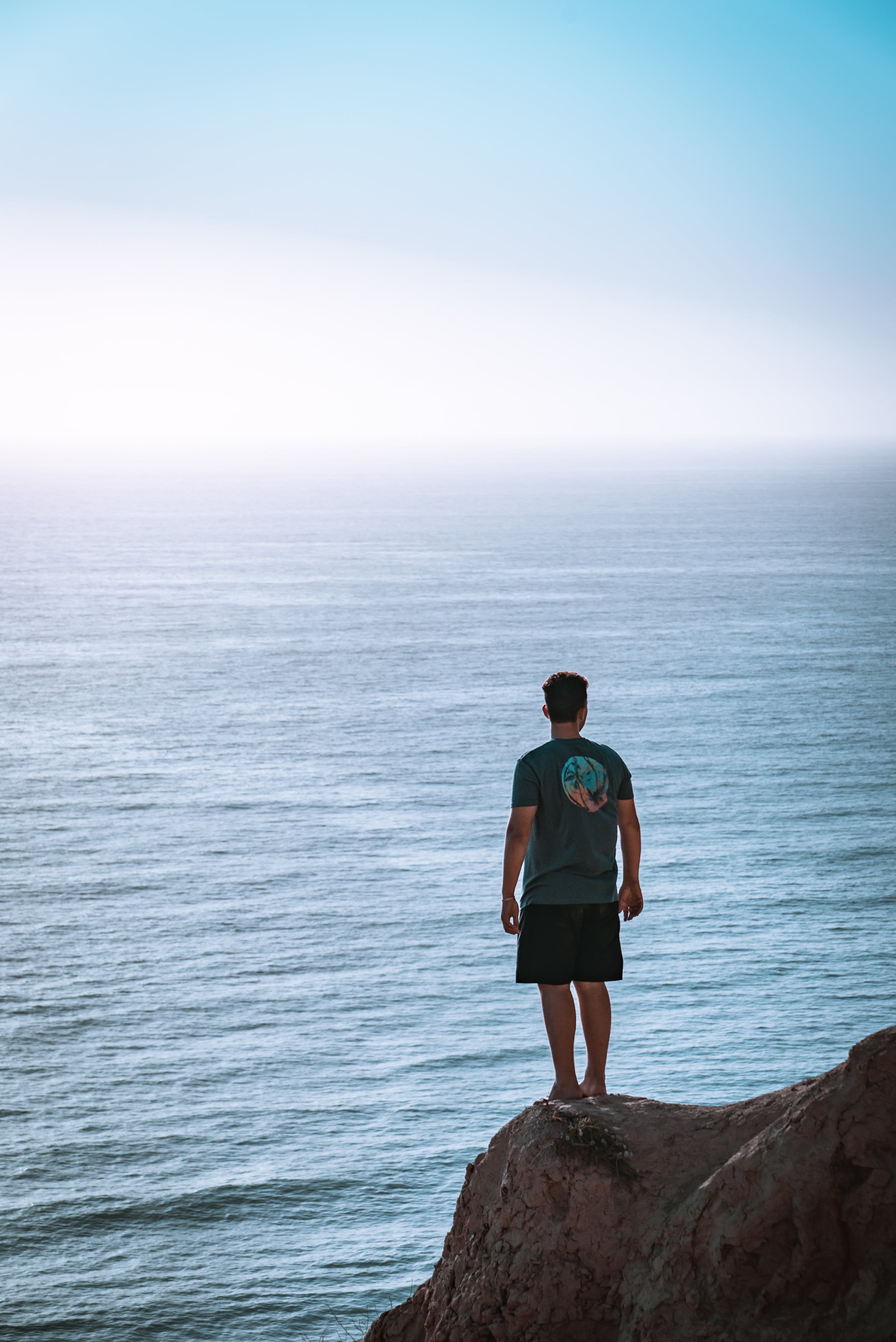 Man Standing on Cliff Near Sea