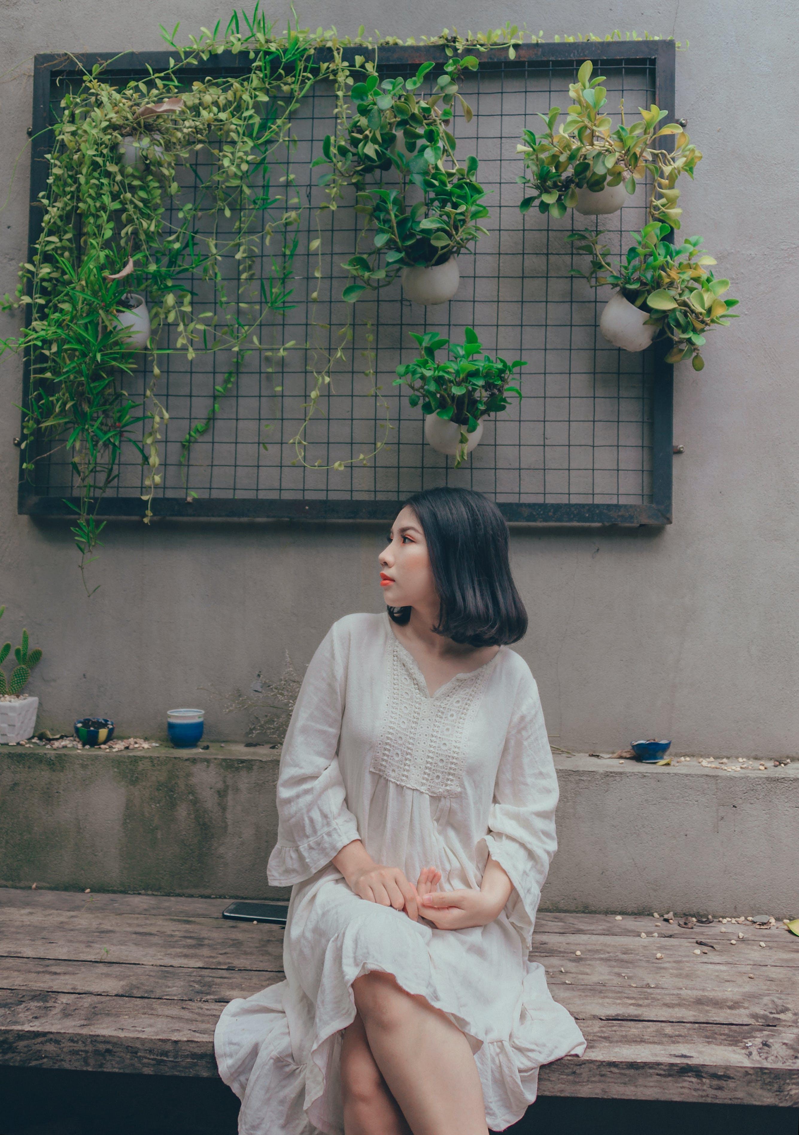 Woman In White V-neck Long-sleeved Dress Sitting On Bench