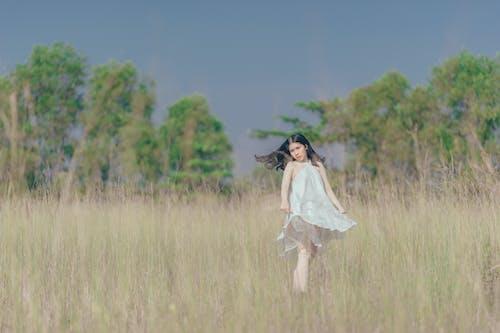 Woman In White Halter Dress On Grass Field