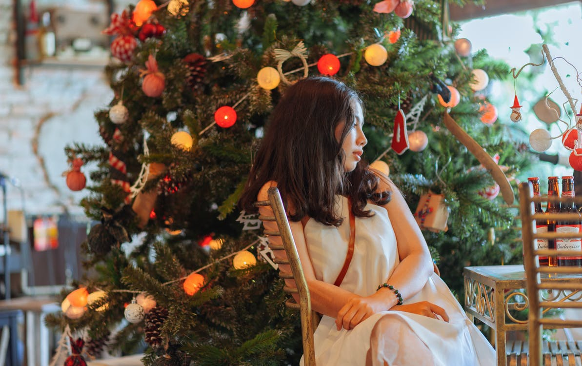 Woman Wearing White Dress Sitting Near Christmas Tree