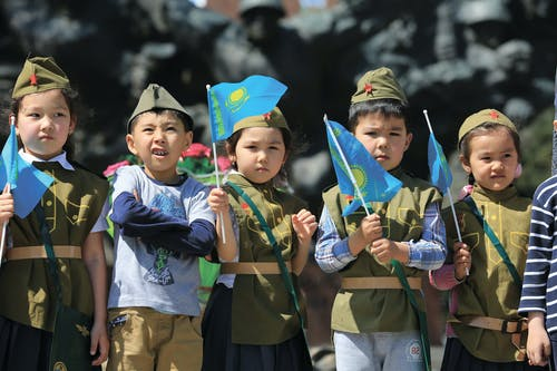Five Boys Holding Blue Flags
