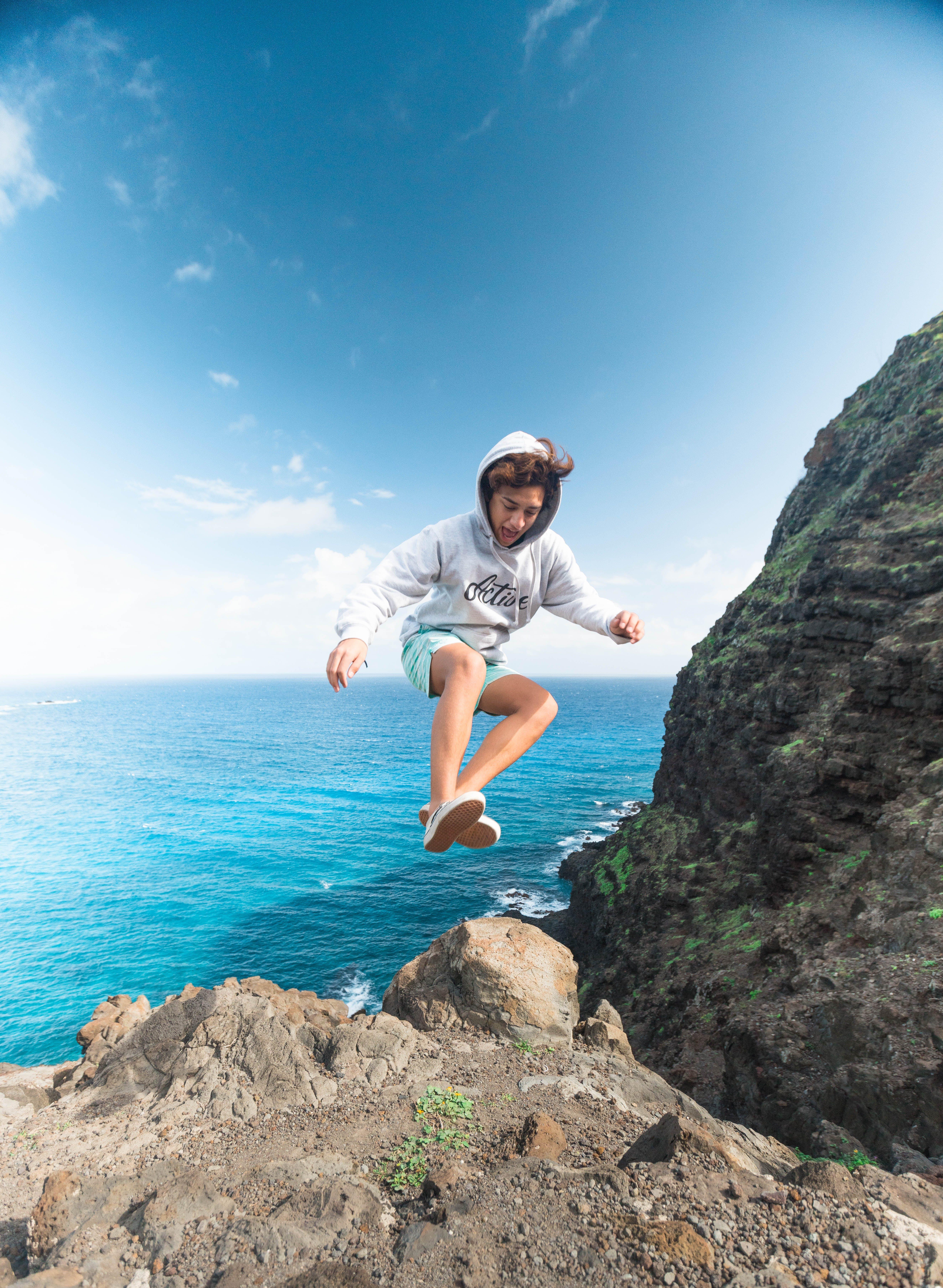 Man Wearing Gray Hoodie Jumping at Rock