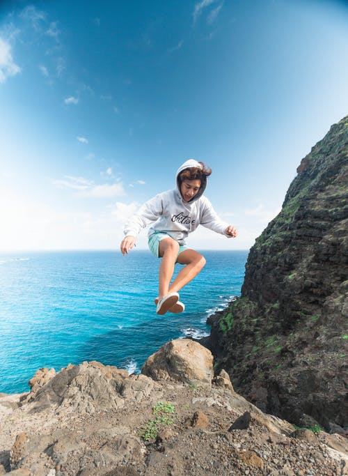 Man Wearing Gray Hoodie Jumping at Rock