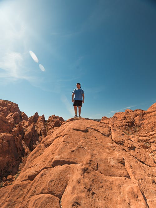Man Wearing Blue Shirt and Black Shorts Standing on Top of Brown Rock Formations Under Clear Sky