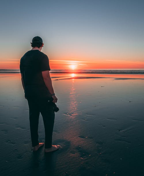 Man Standing on Beach during Sunset