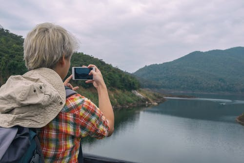 Person Holding Smartphone While Taking Photo of Calm Water Near Mountain at Daytime