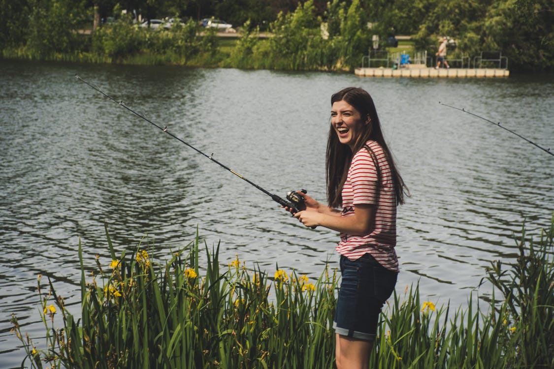 Woman in Red Striped Shirt and Blue Denim Shorts Holding Fishing Rod