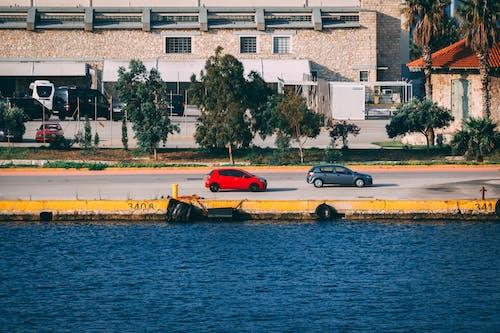 Gratis stockfoto met architectuur, auto's, blauw water, bomen
