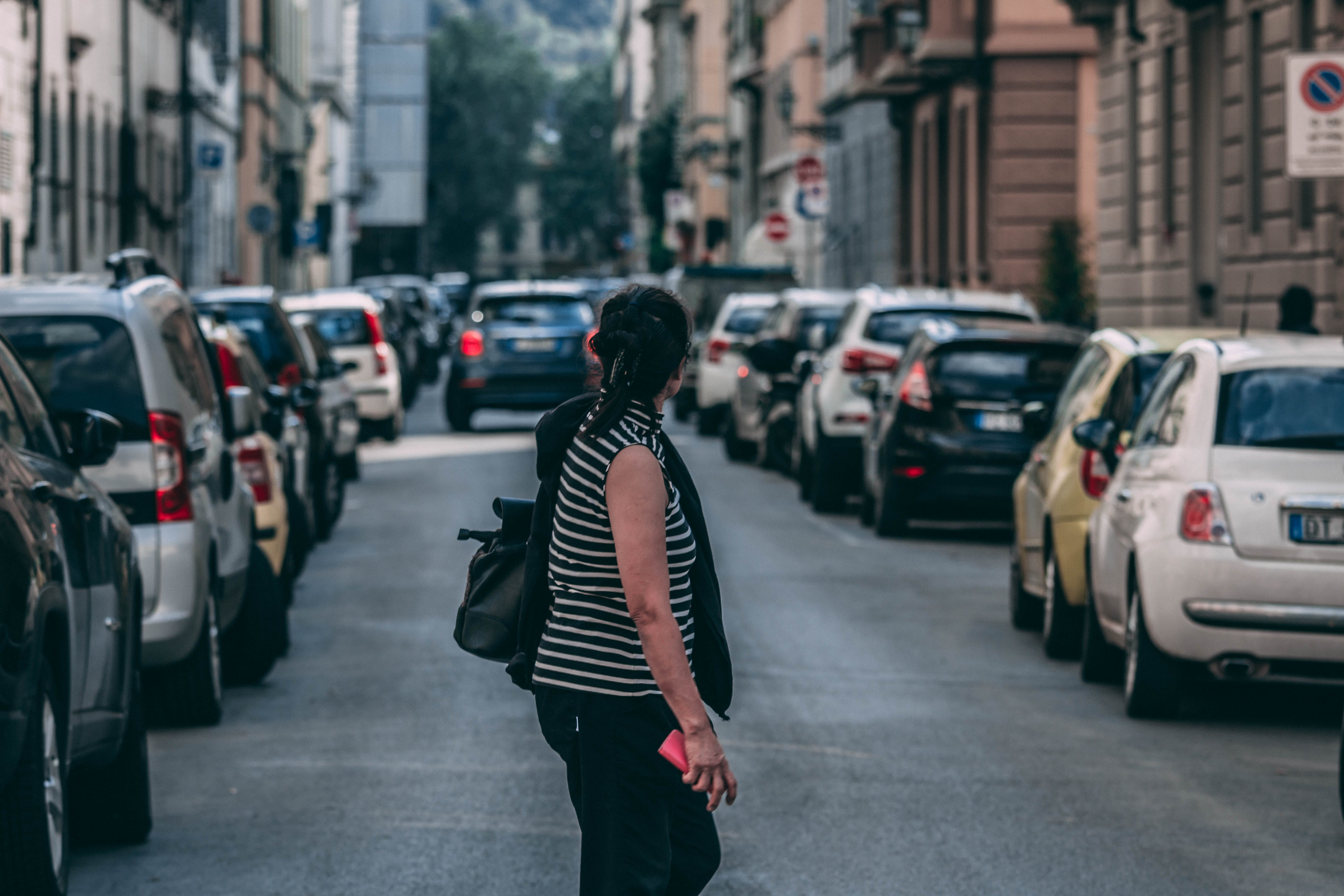 Woman Standing on Road Between Part Cars