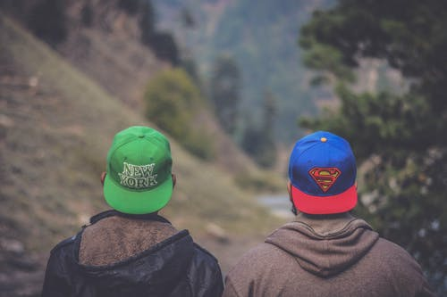 Shallow Focus Photography of Two Men Wearing Caps