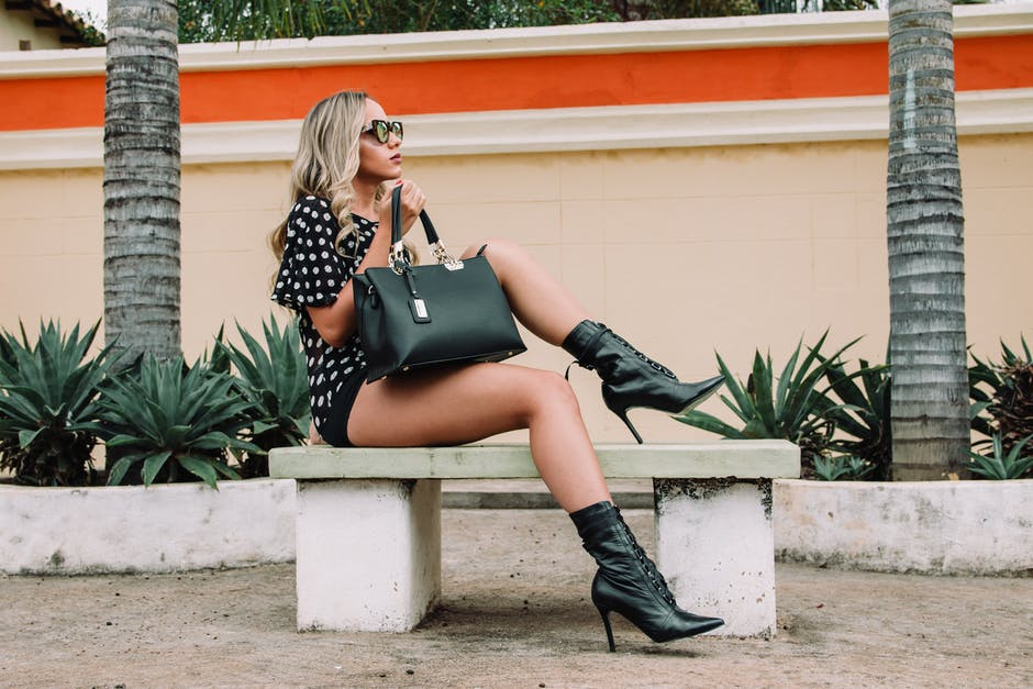Woman wearing black and white polka dot shirt with black short shorts holding black leather tote bag...