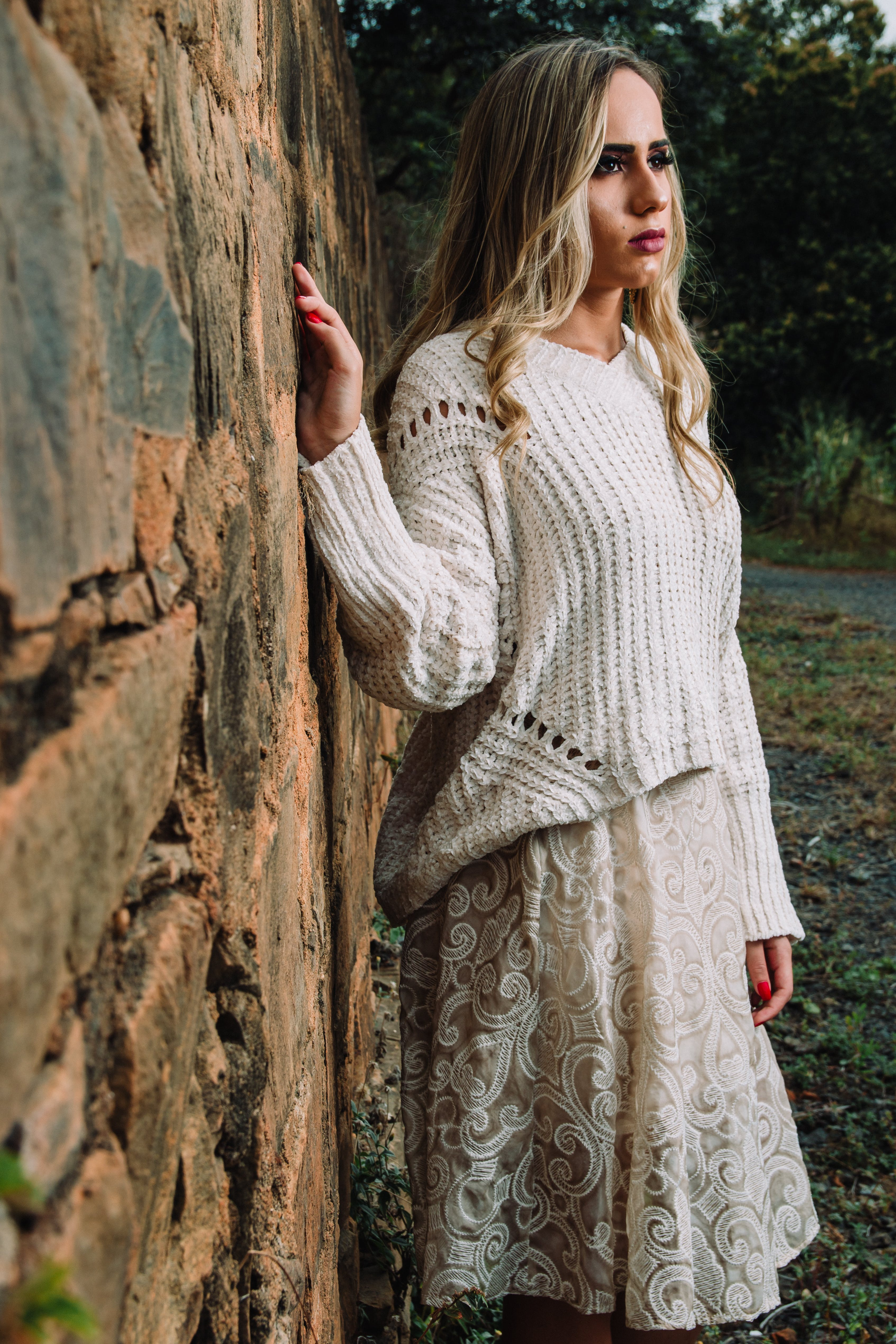 Woman in Knitted V-neck Long-sleeved Shirt and Midi Skirt Standing Beside Wall