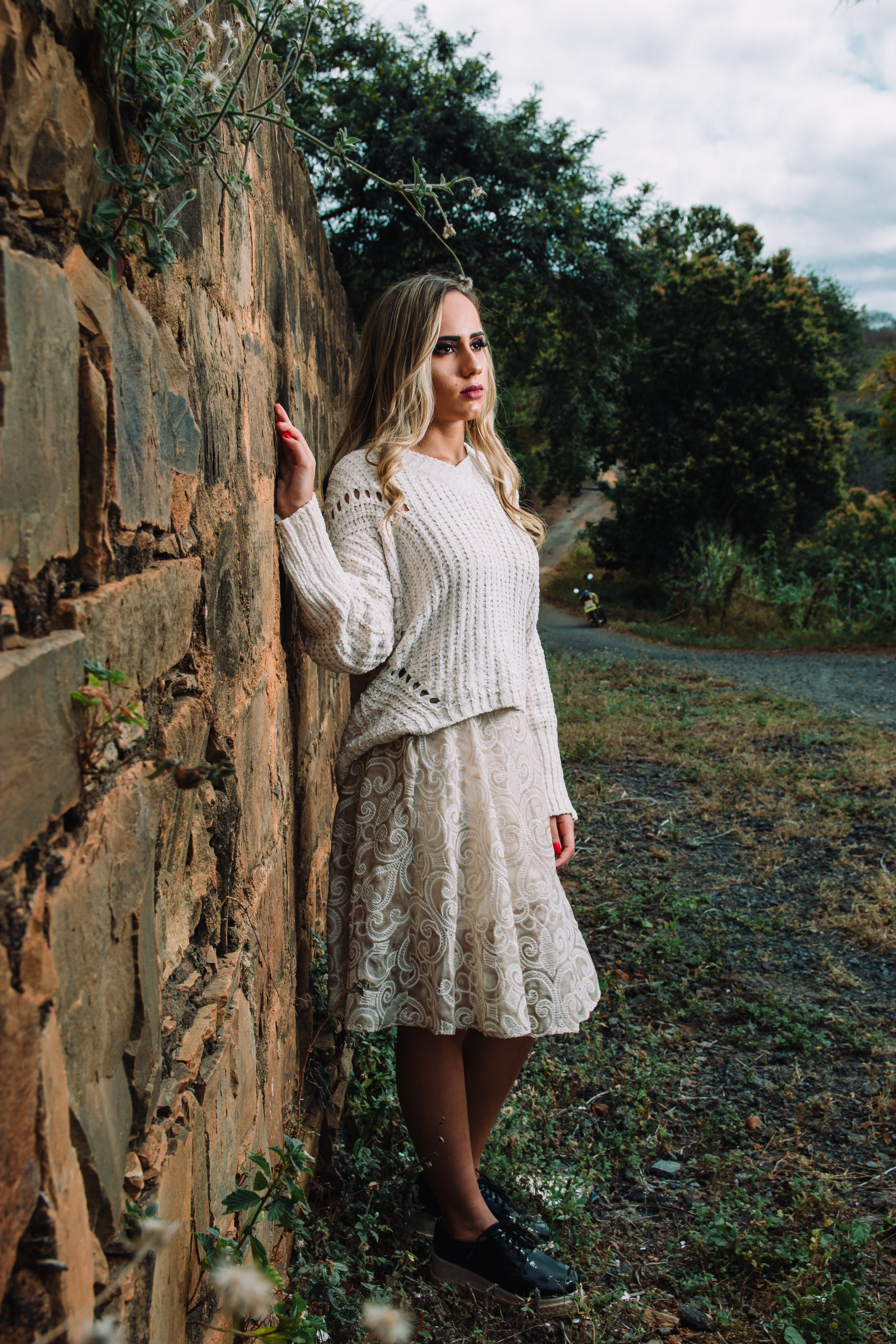 Photo of Woman in White Long-sleeved Shirt Beside Concrete Wall