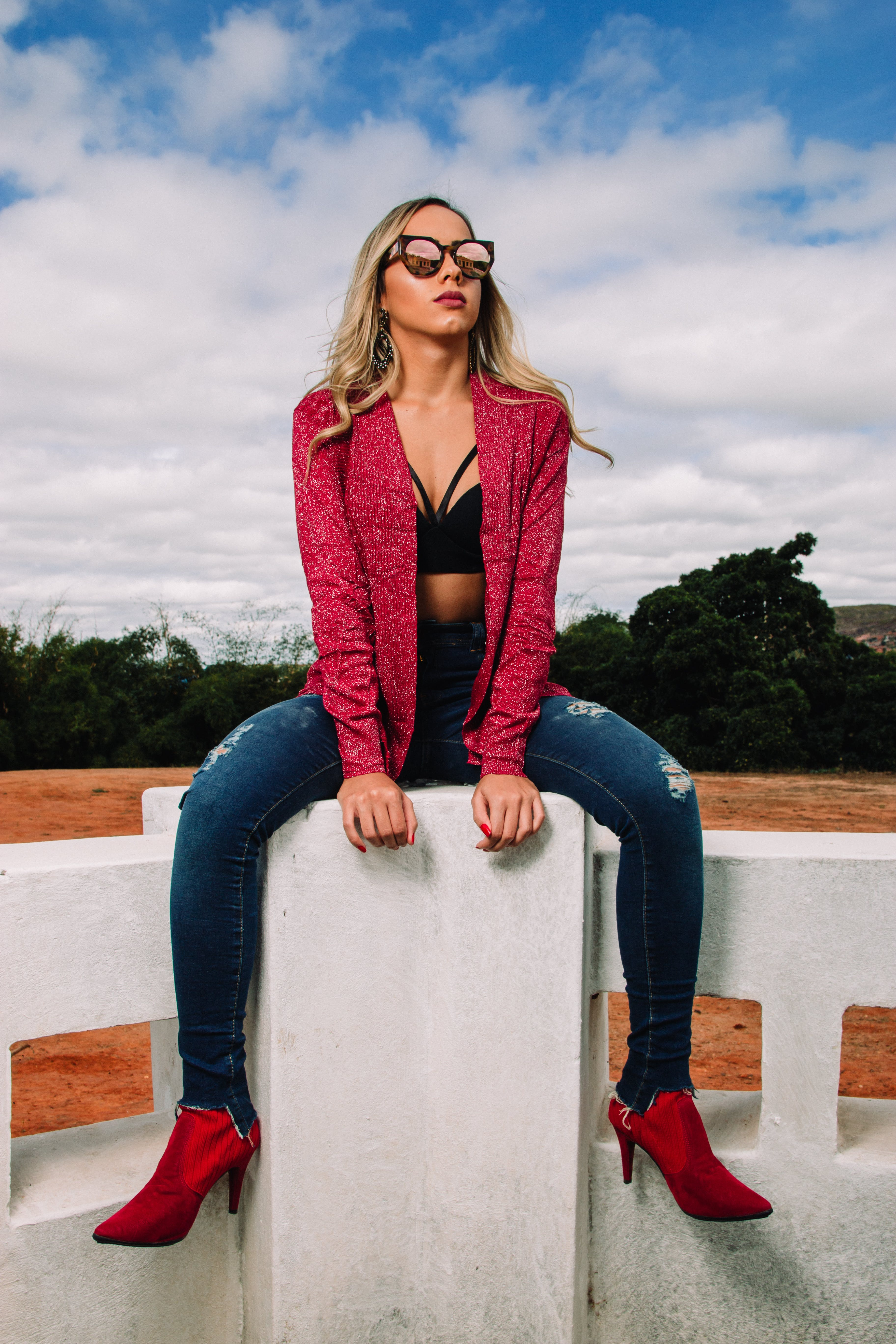 Woman Wearing Red Jacket and Distressed Blue Denim Skinny Jeans Sitting on Bench
